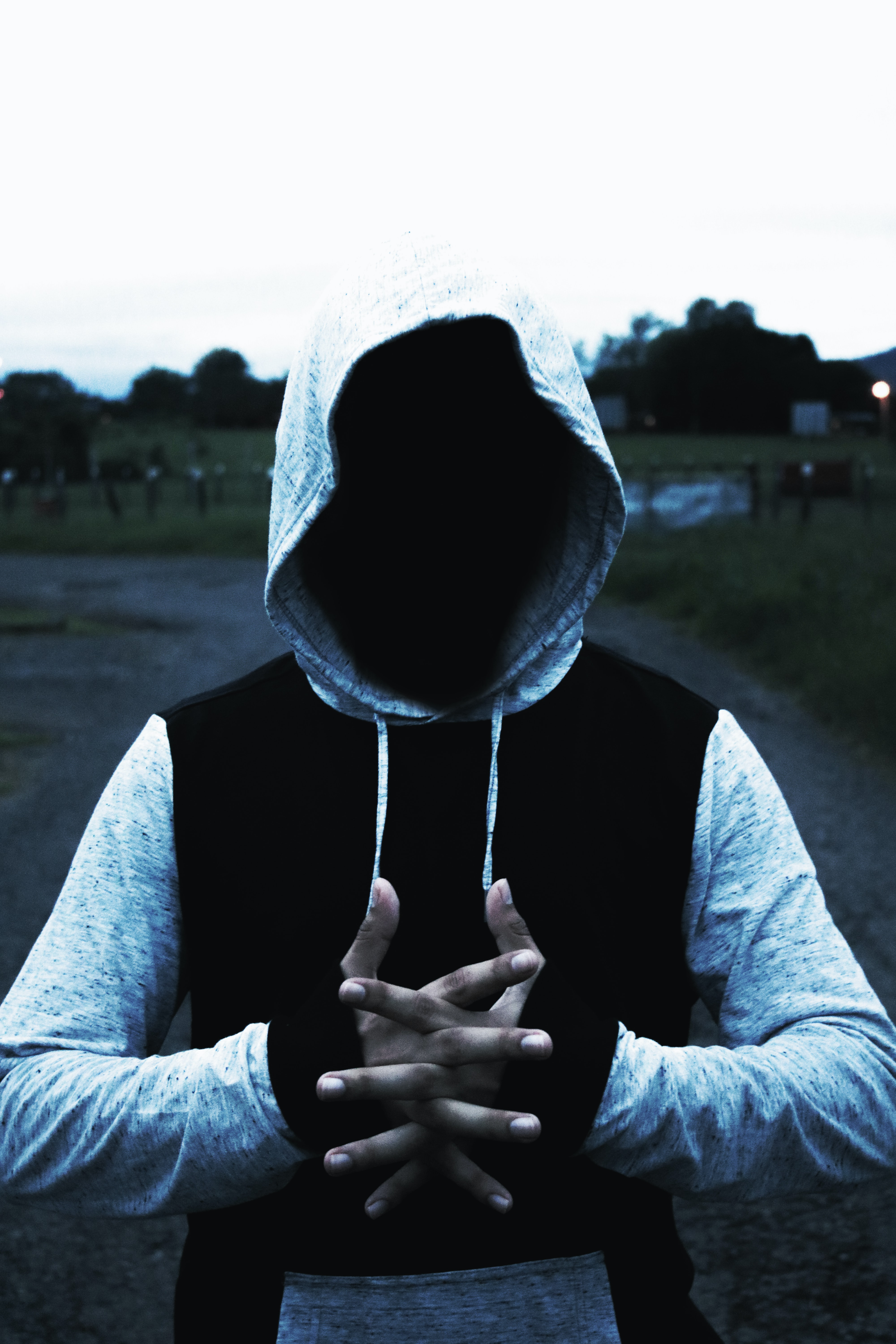 A hooded man stretches his hands.
