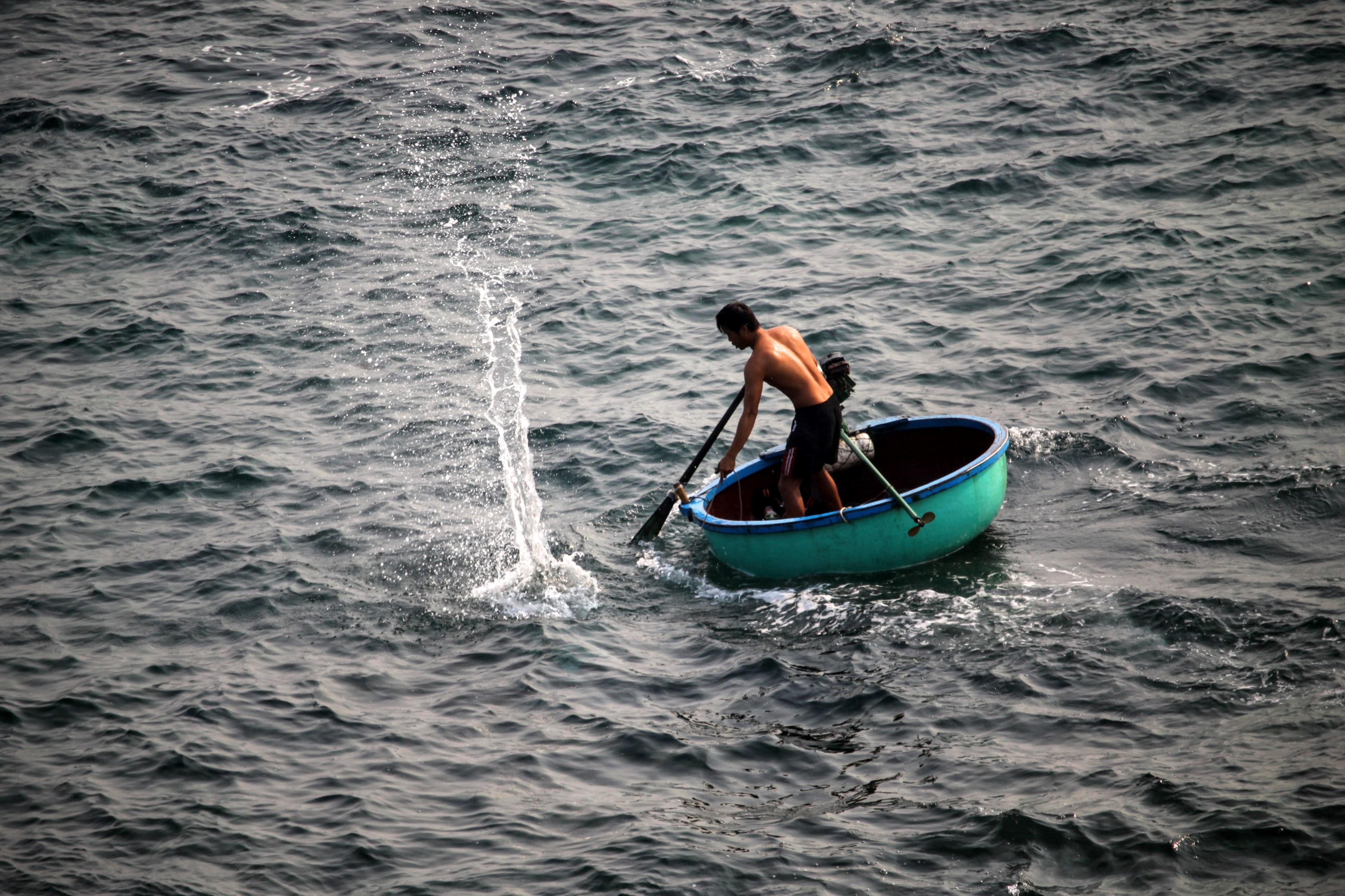 A fisherman paddling a turquoise boat in Quảng Ngãi
