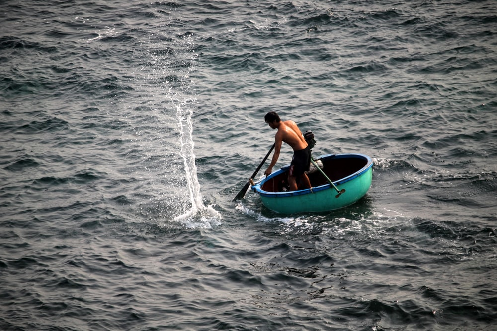 man riding on round green boat at daytime