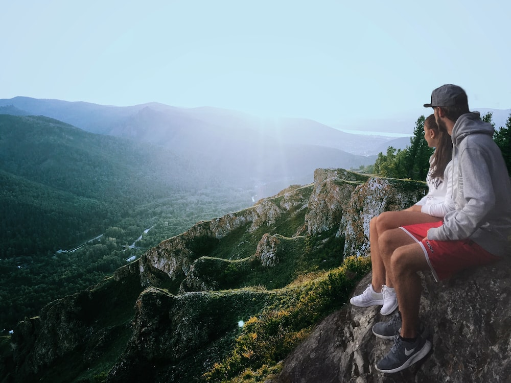 couple sitting on edge while looking at the mountains