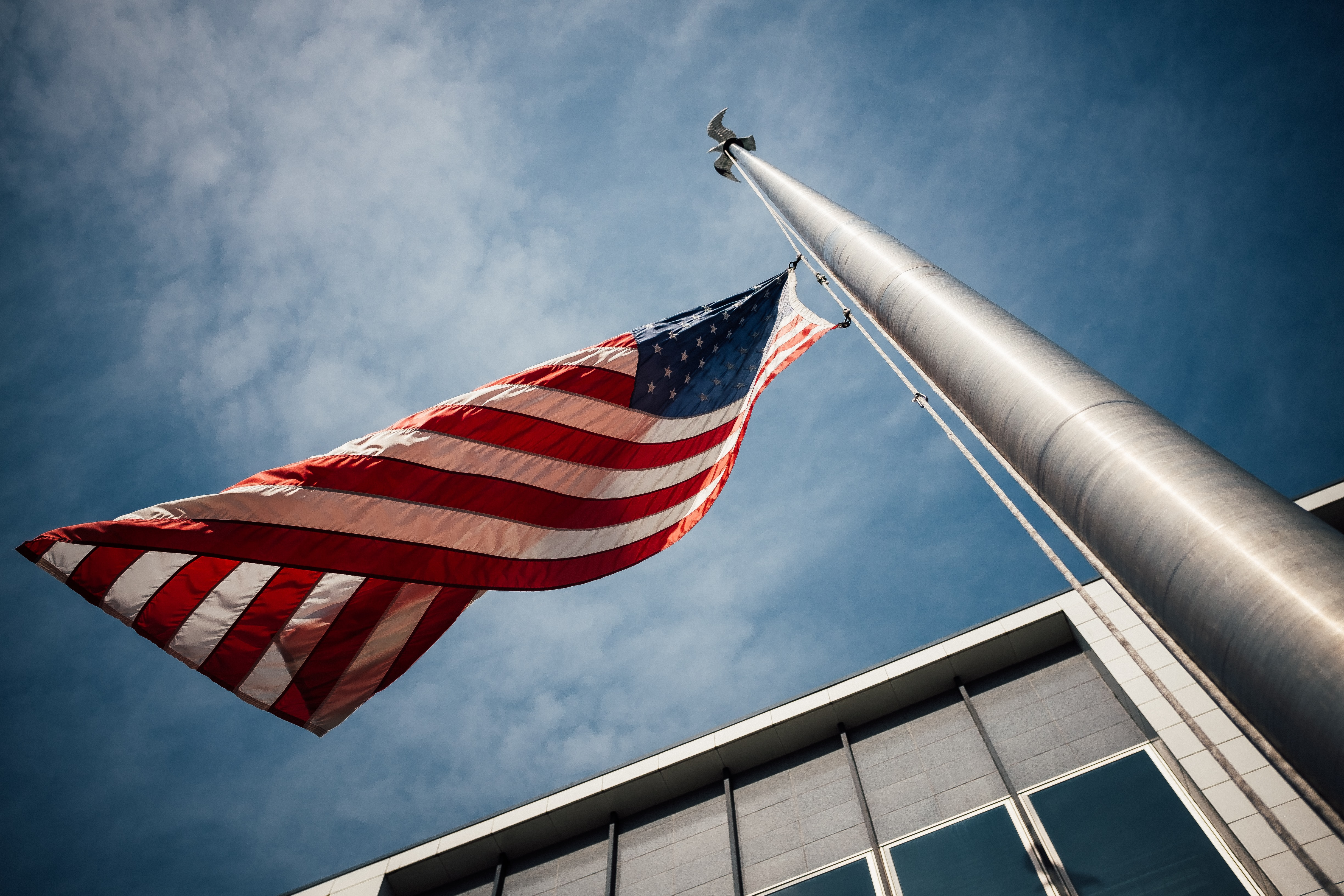 Looking up at a flagpole with the American flag flying half mast