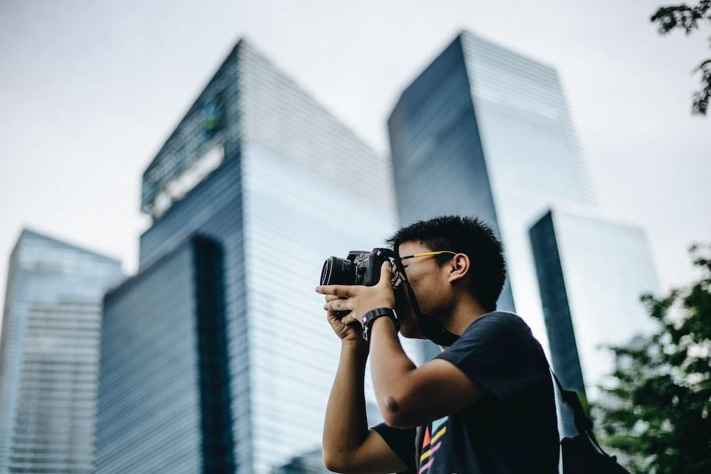 man wearing black t-shirt holding DSLR camera