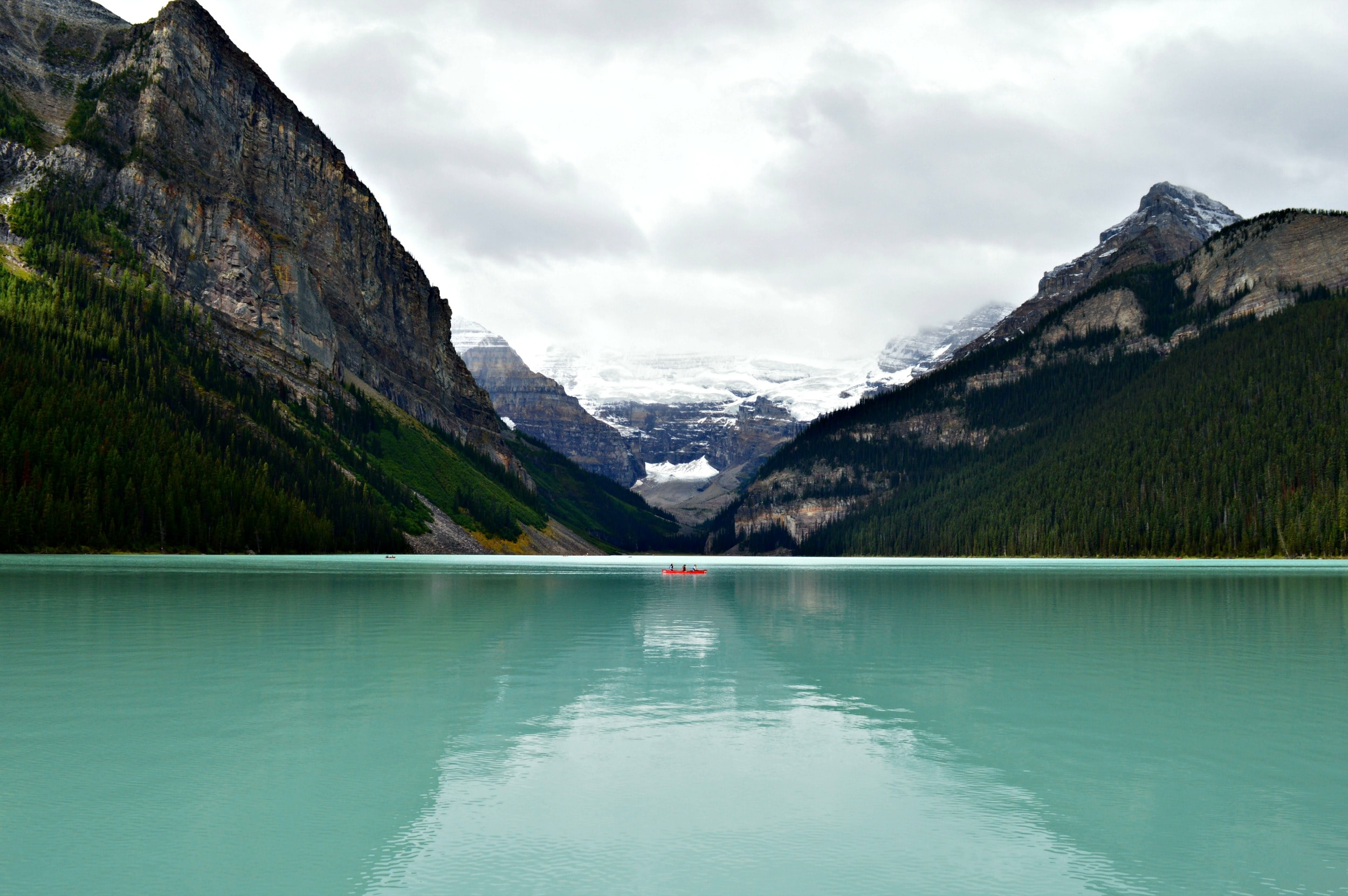 A red boat on the turquoise surface of Lake Louise surrounded by jagged mountains