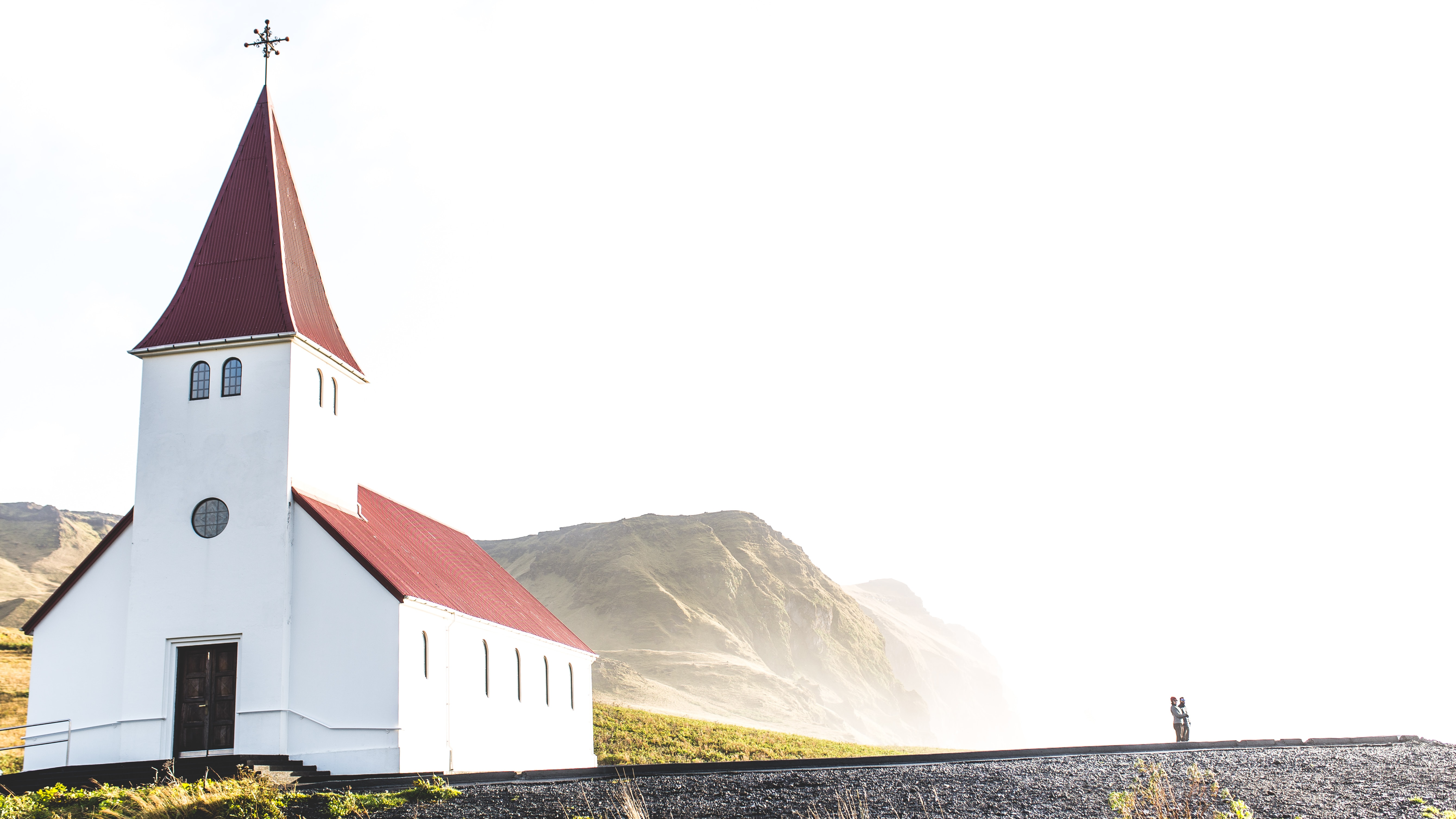 red and white concrete church near gray mountains under cloudy sky