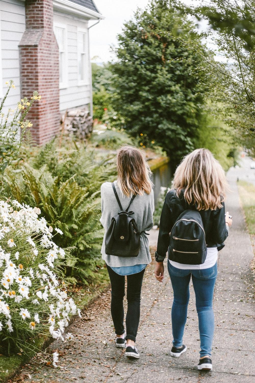 two ladies walking on sidewalk with black backpacks