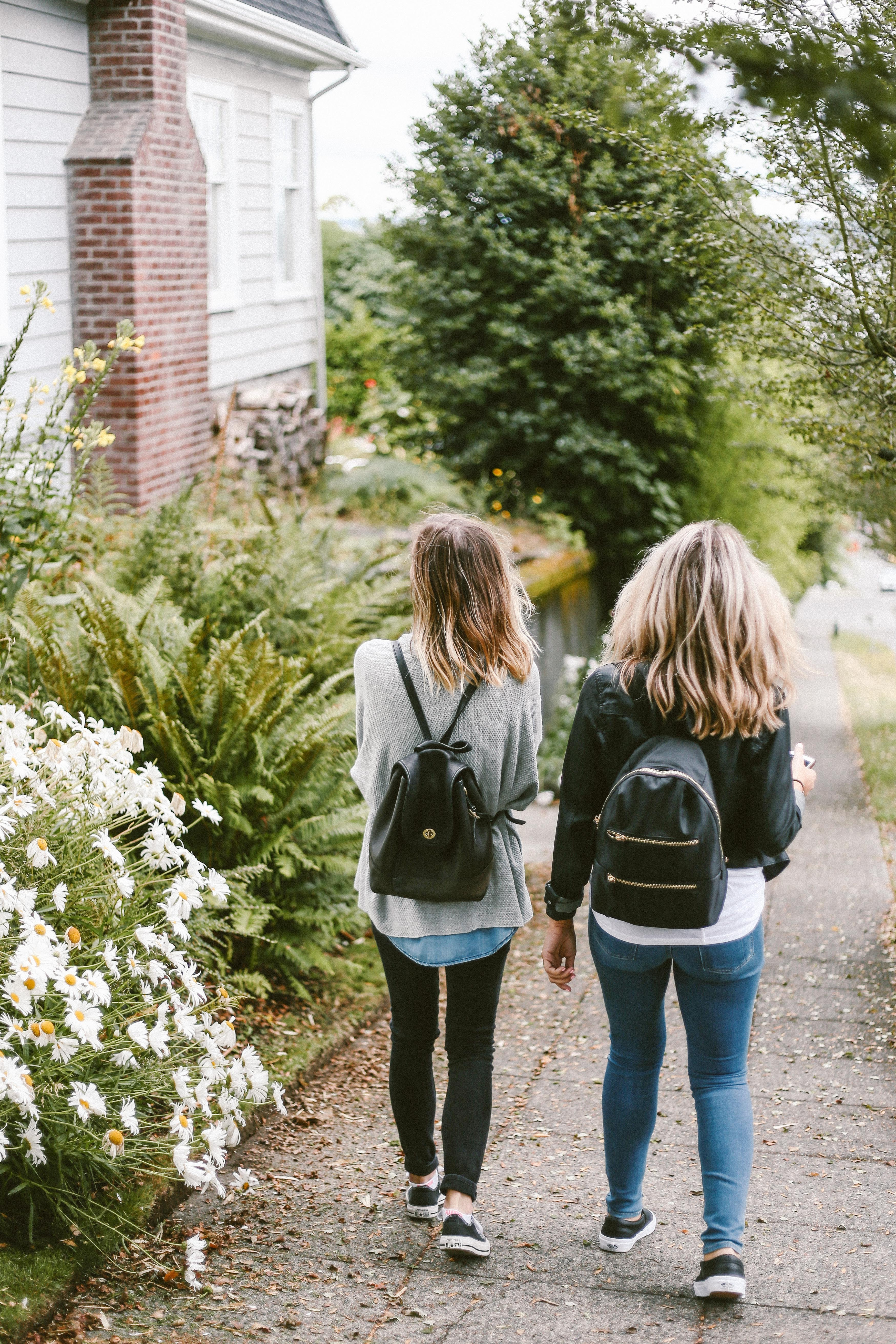 two ladies walking on sidewalk with black backpacks
