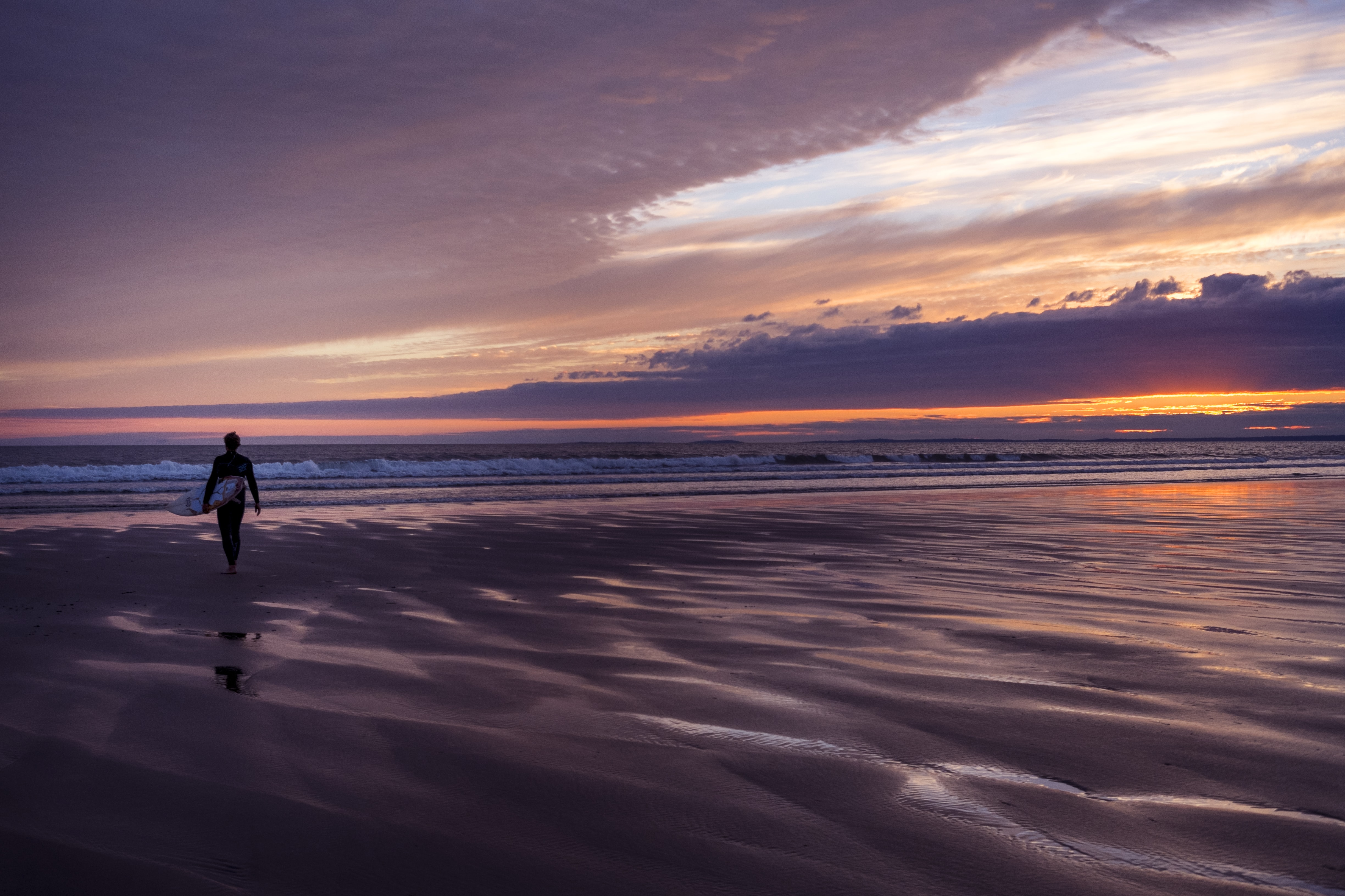 A surfer in a wetsuit walking across a beach at sunset towards the sea, with the sun behind a cloud causing a purple sky