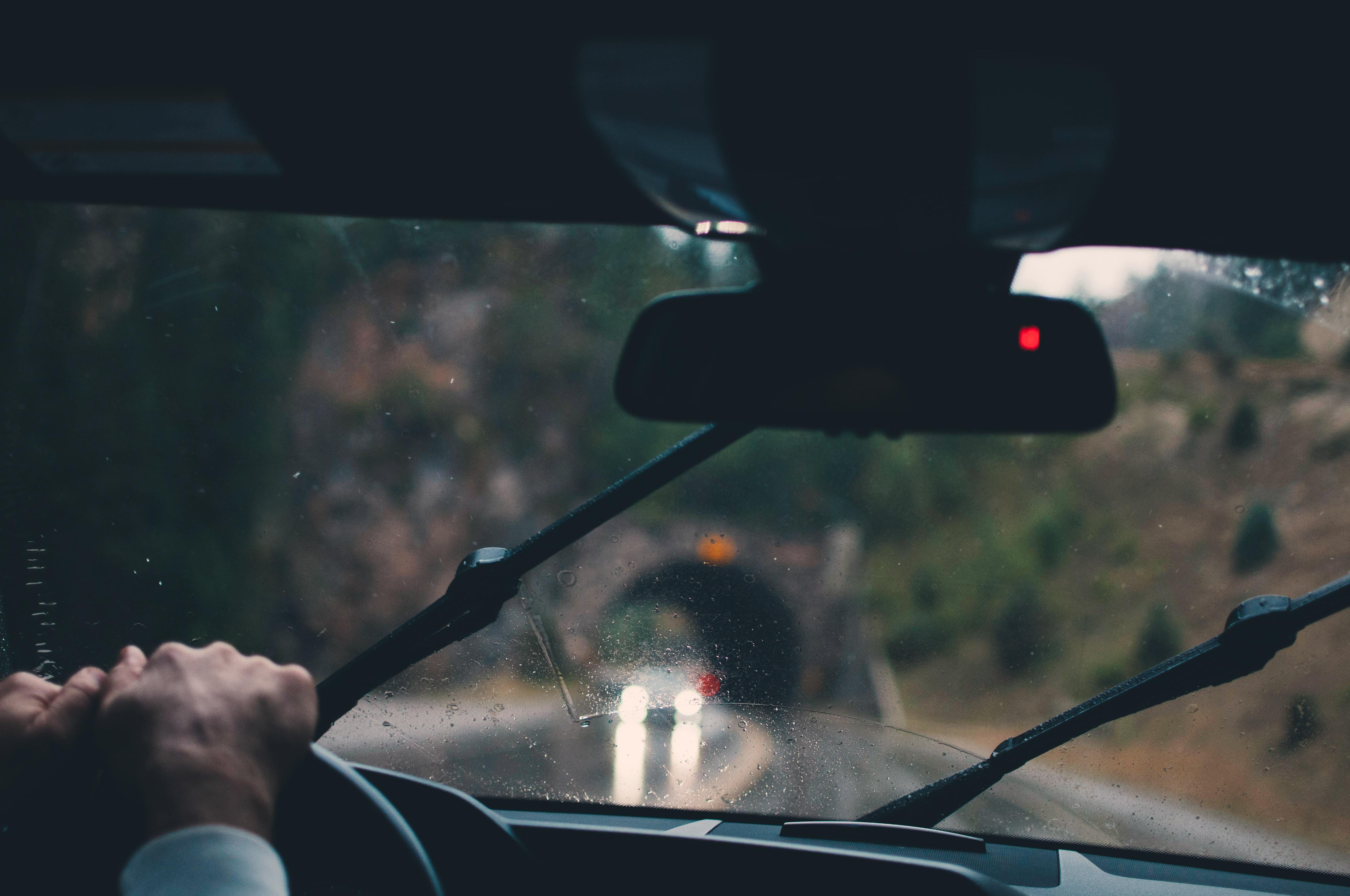 foto do interior de um carro com uma mão no volante