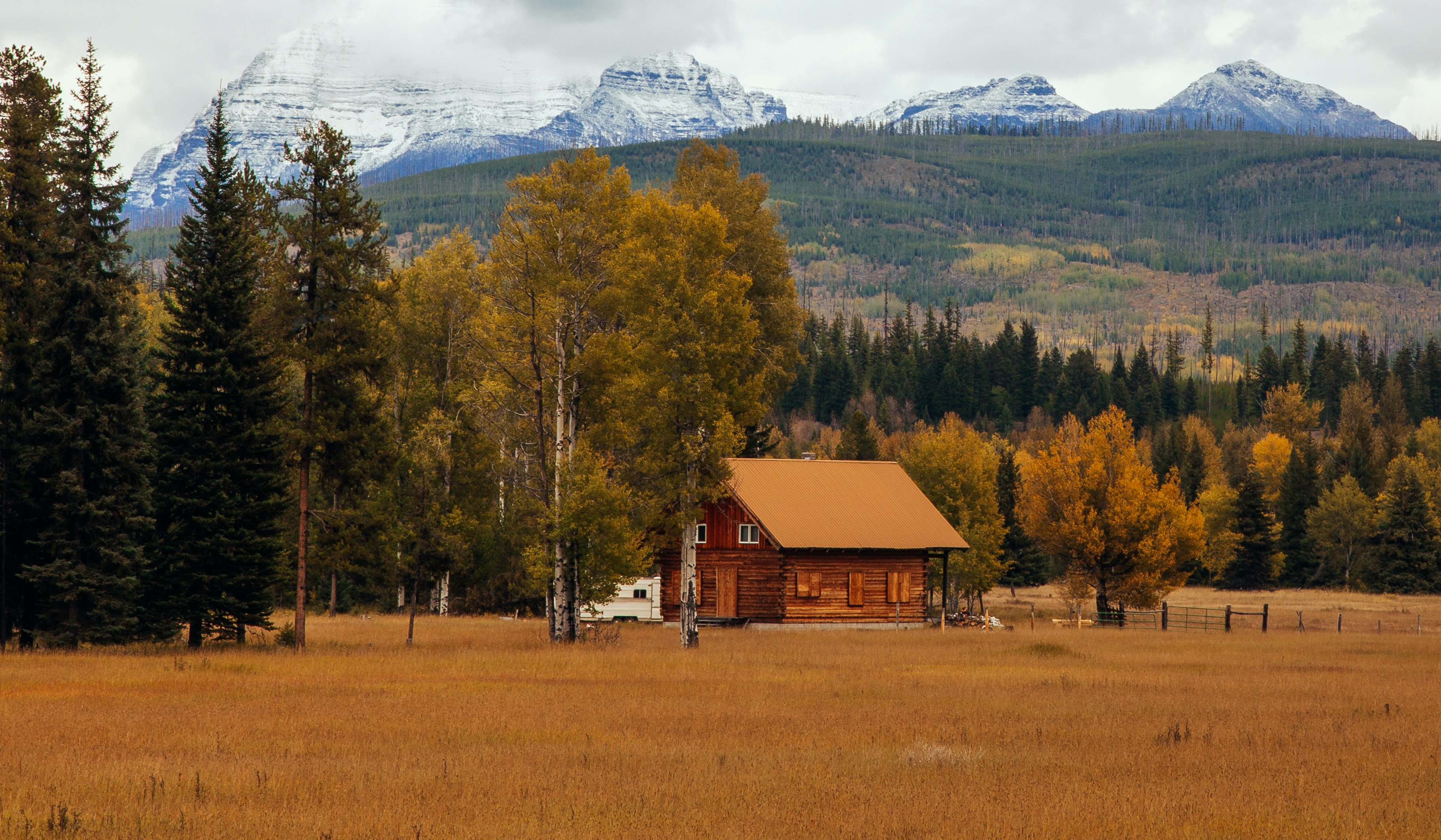 Small log cabin house in Glacier National Park at the edge of a forest and field with snow capped mountains in the background