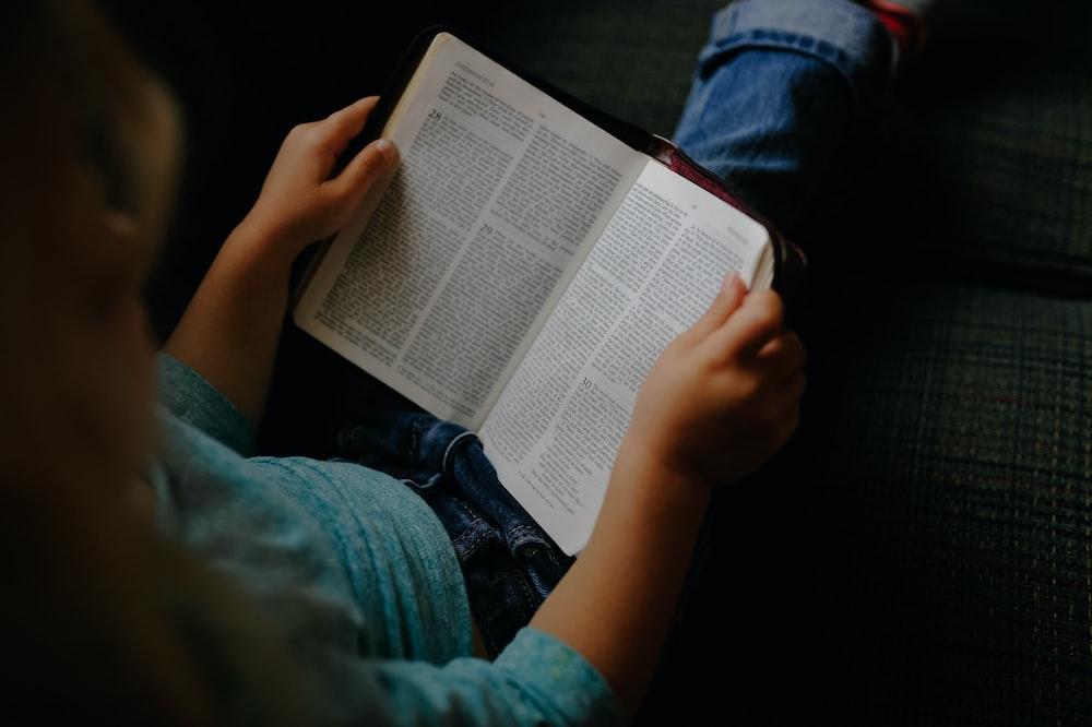 toddler girl reading a book at vehicle backseat