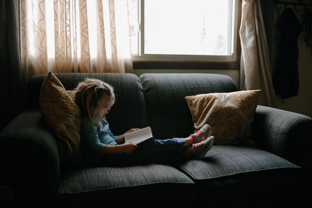 girl reading book sitting on sofa