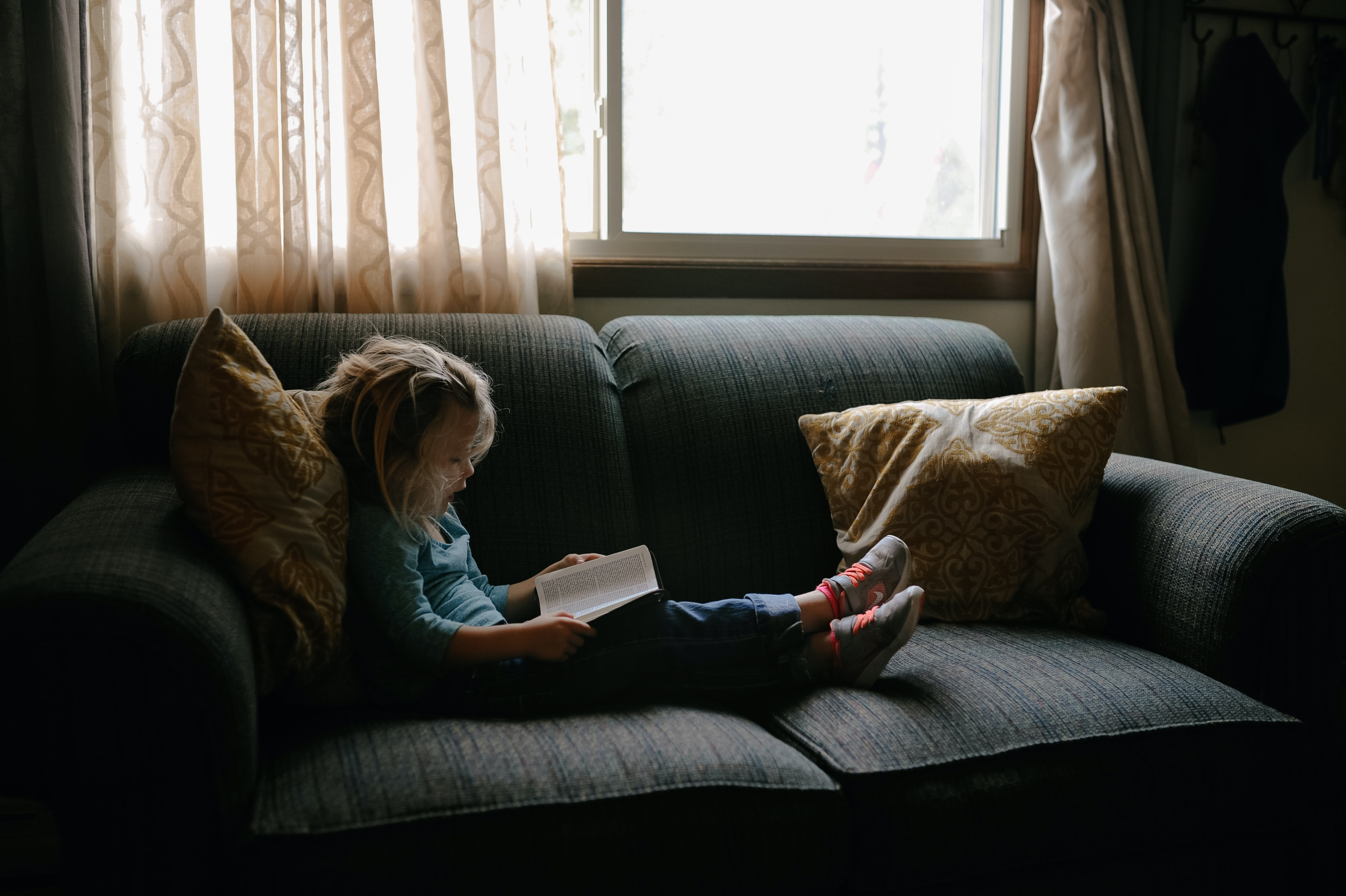 girl reading book sitting on sofa