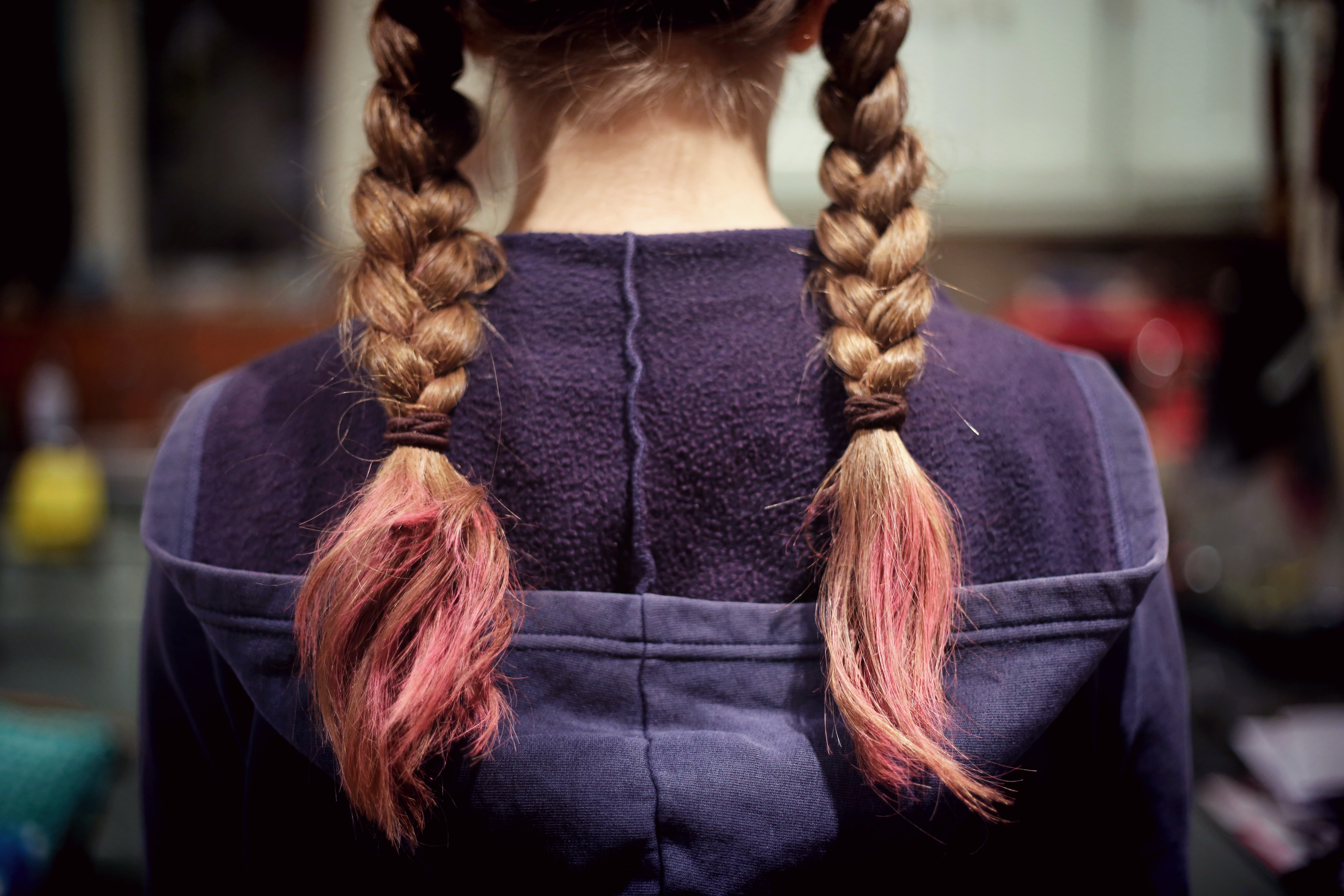 Standing behind a girl whose hair is in braided pigtails with pink ends