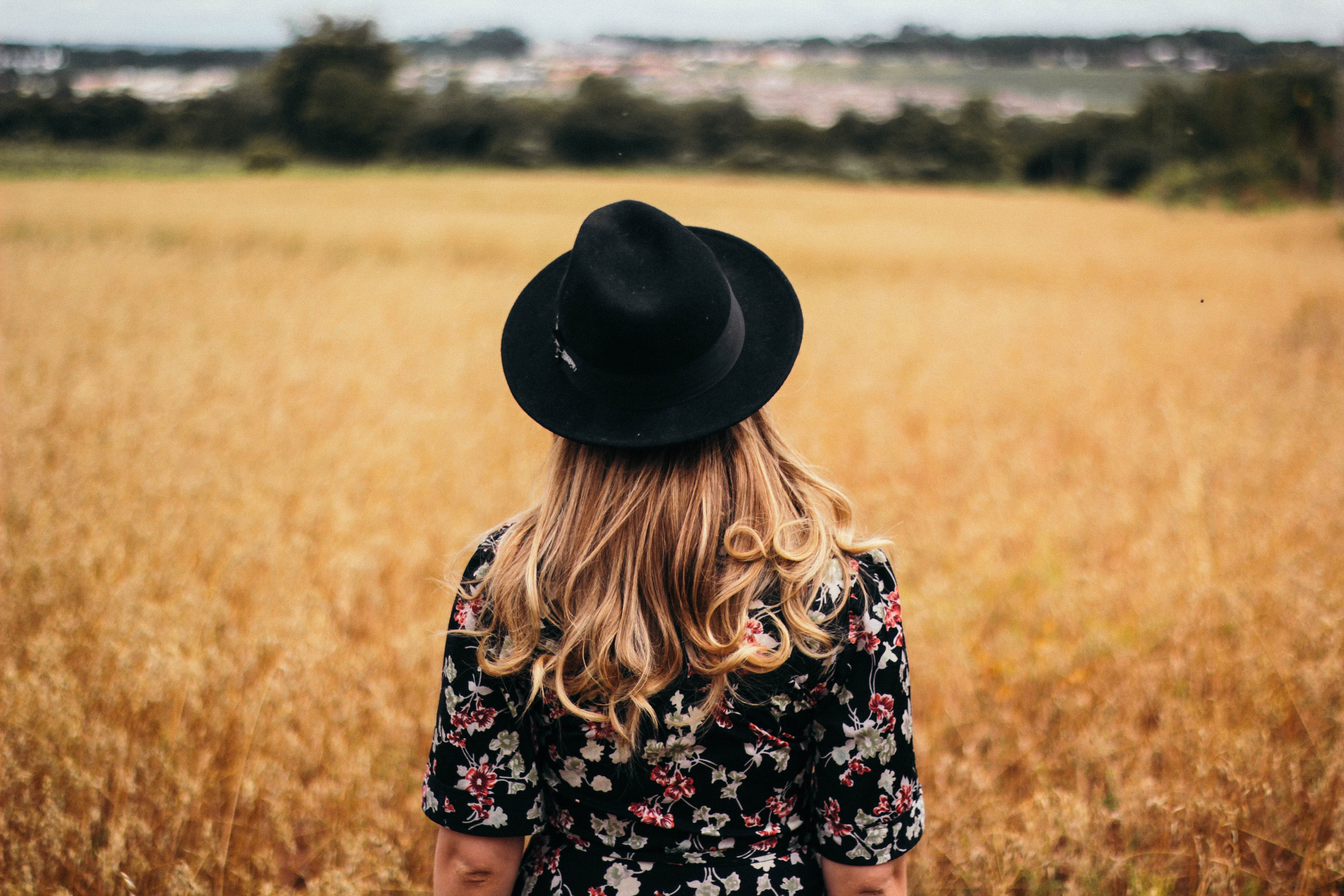 Behind a woman standing alone in a wheat field waring a hat and dress