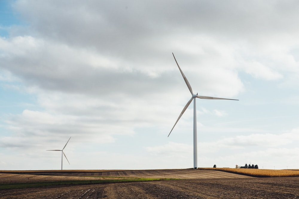 two white windmills on brown field during daytime