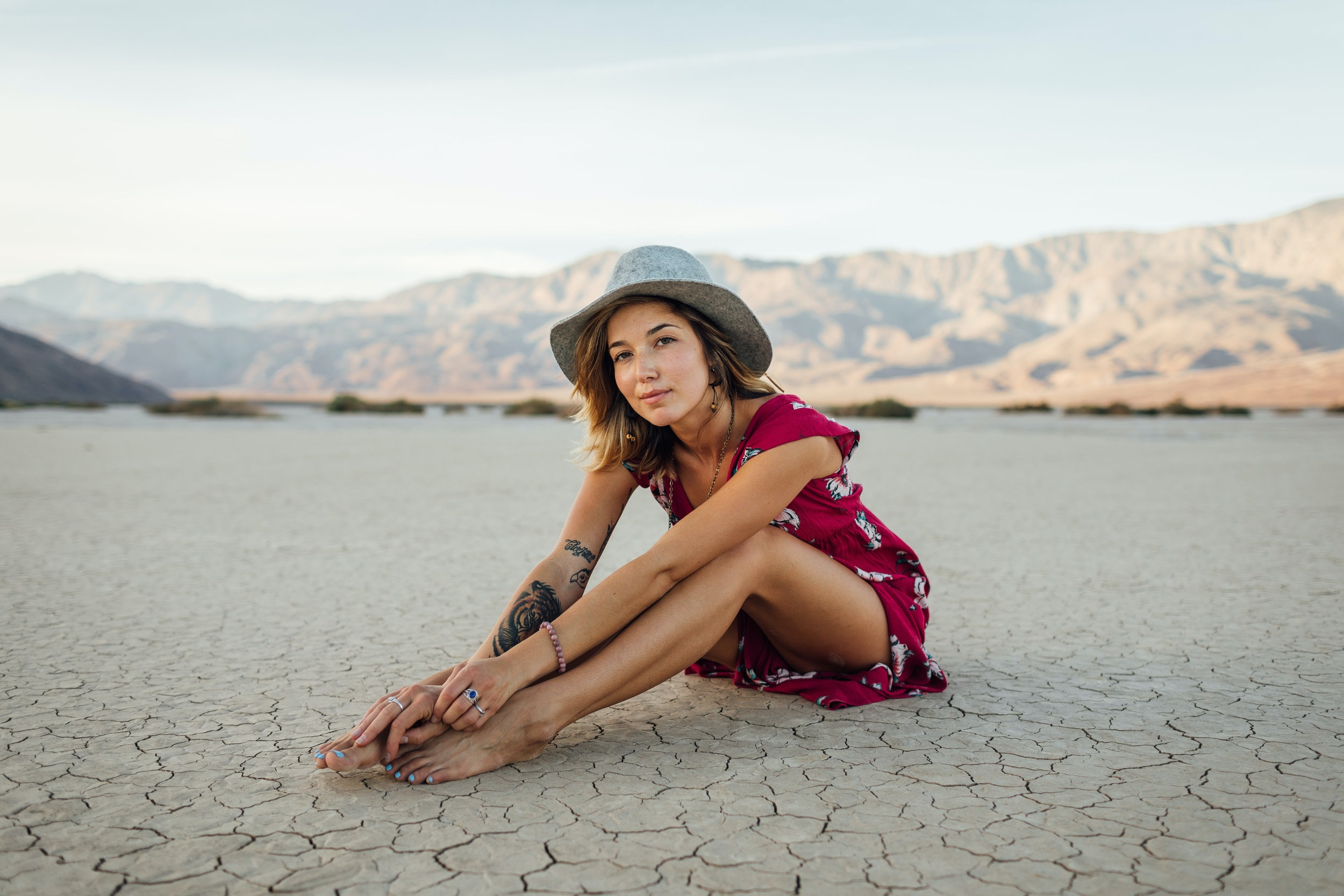 photo of sitting woman wearing red dress and grey cowboy hat with black tattoo in her right arm