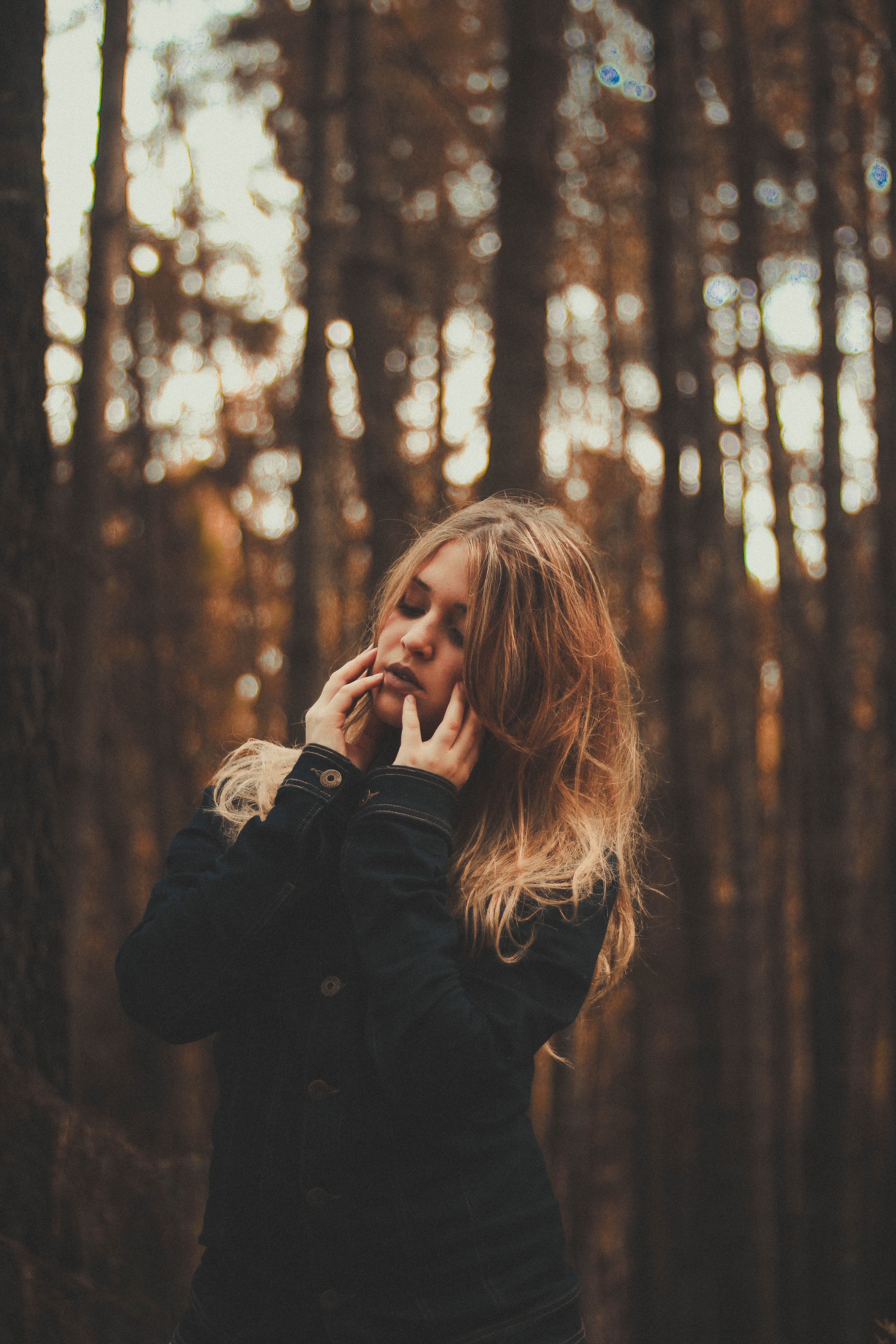 portrait photography of woman wearing black coat surrounded by forest trees during daytime