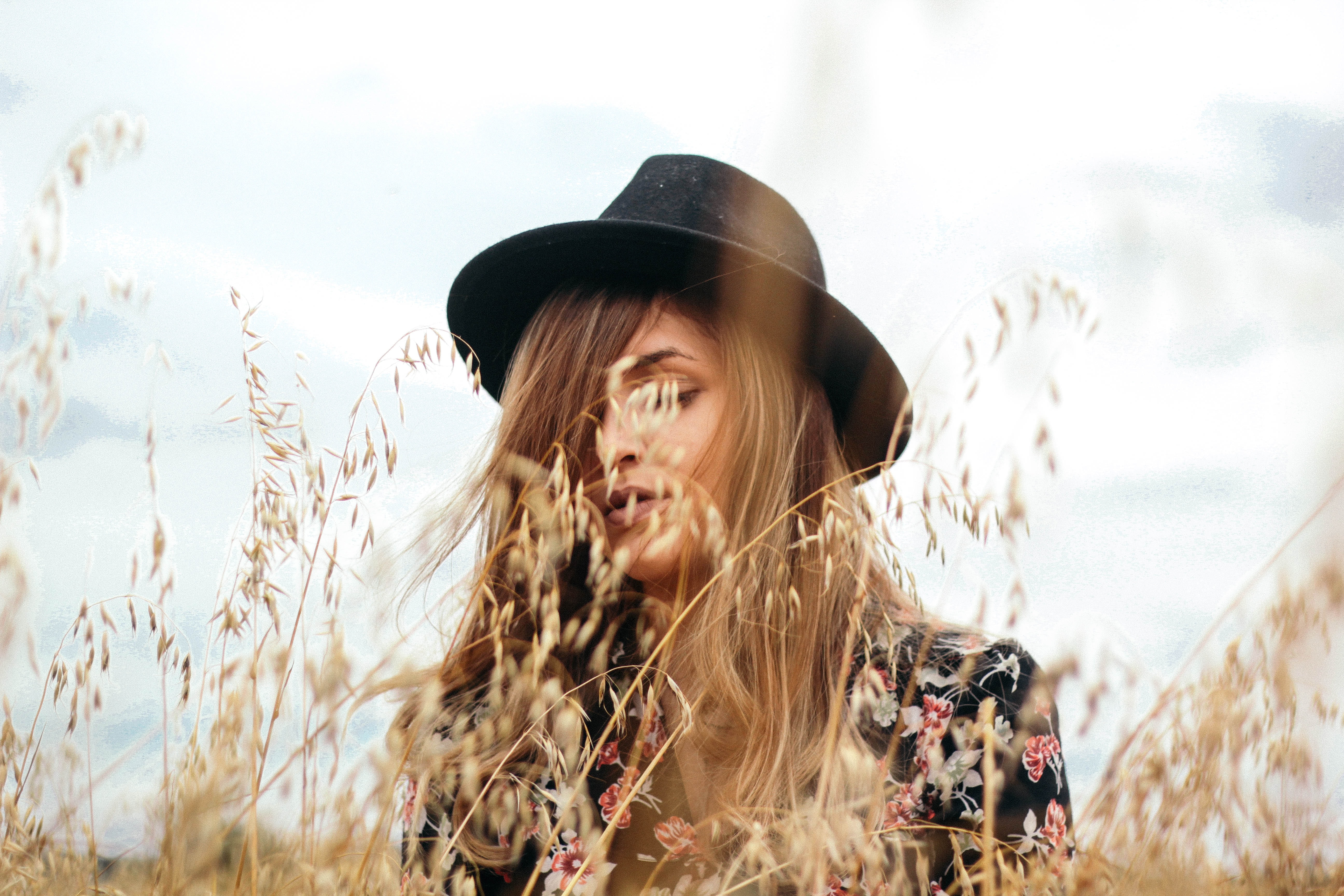 Woman with a black hat standing behind grains of wheat