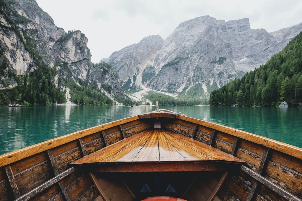 brown wooden boat moving towards the mountain