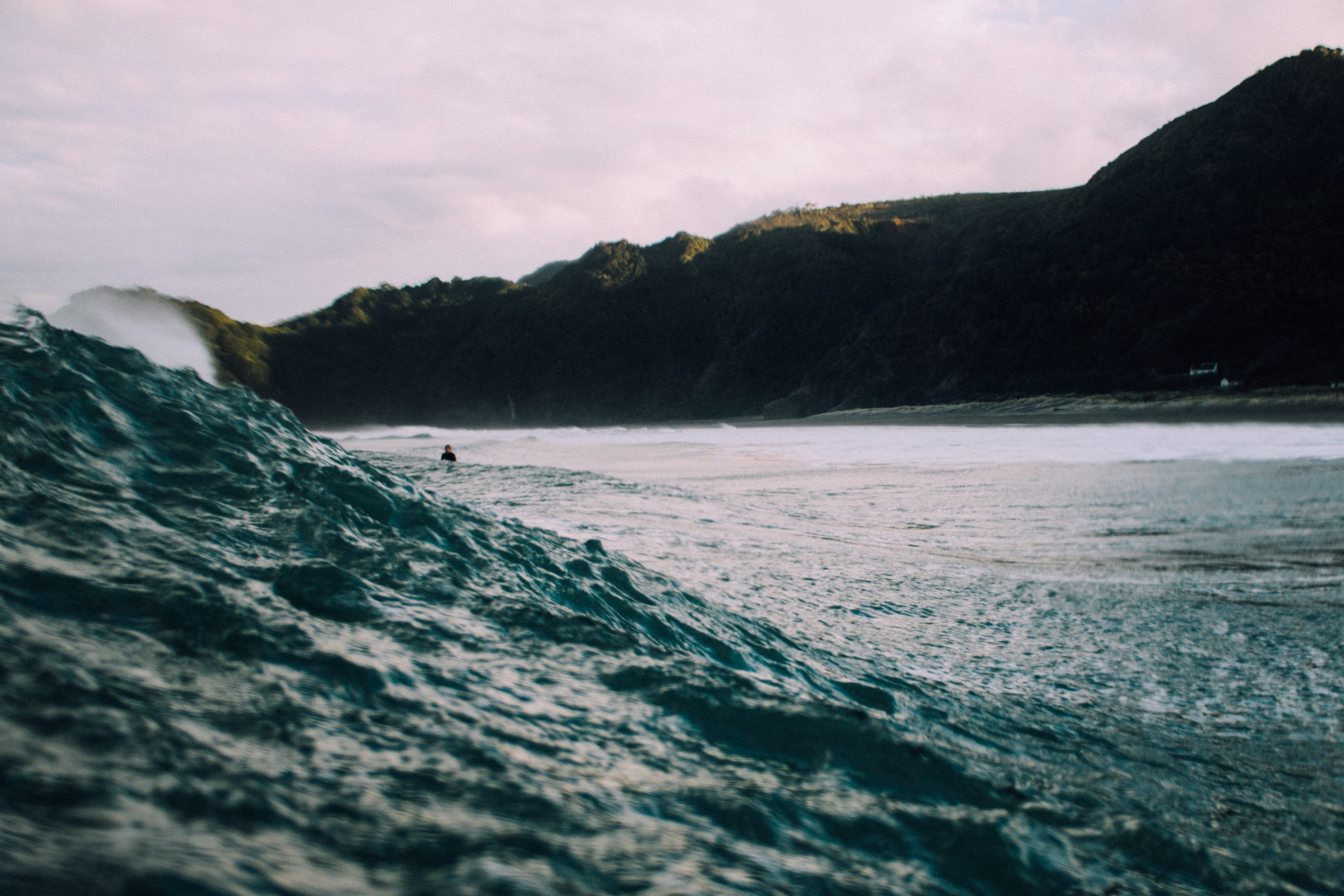 A shot of a rolling wave with a surfer in the distance, and the mountains in the background at Piha