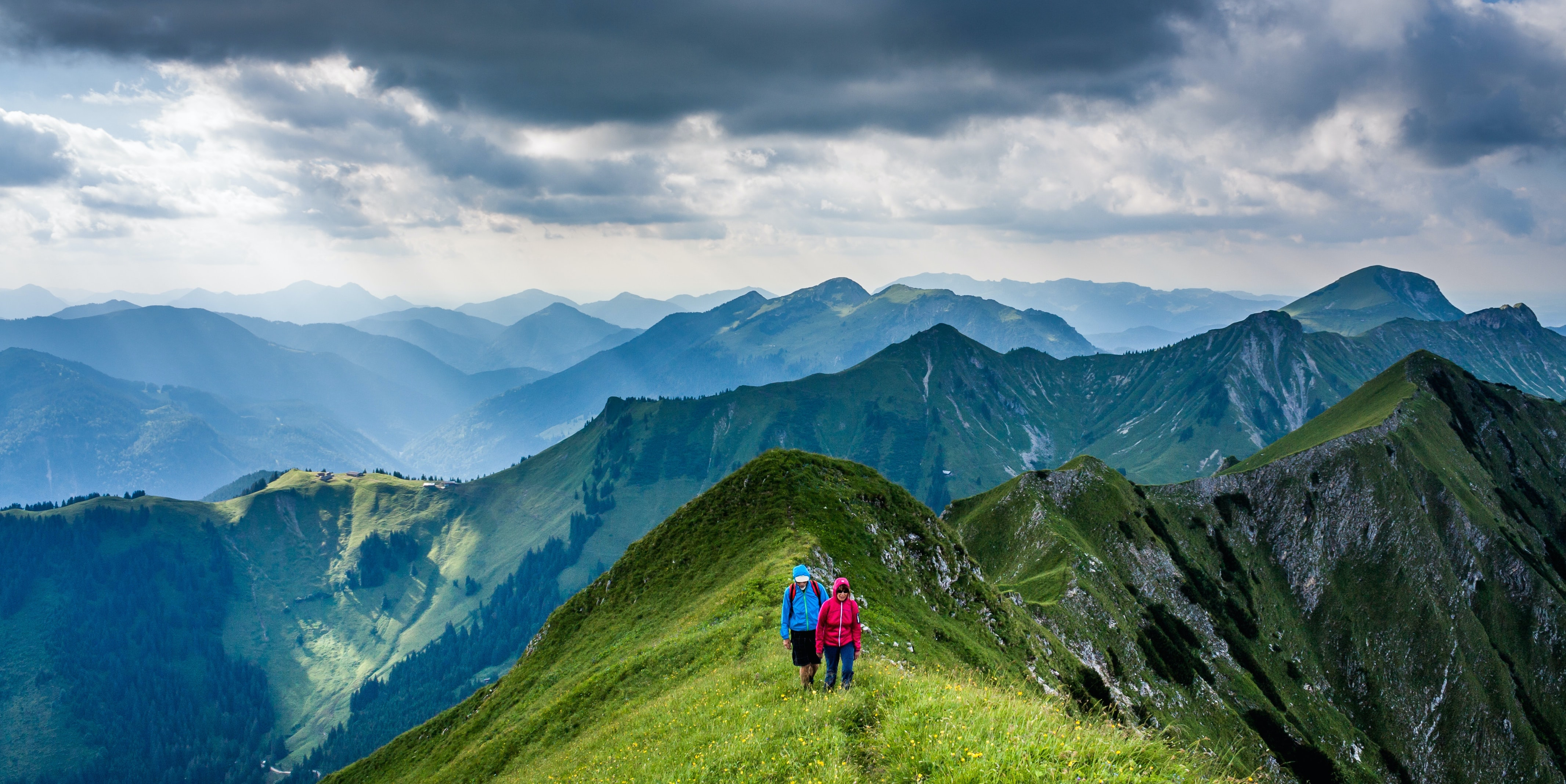 Two hikers walking on a grassy mountain ridge