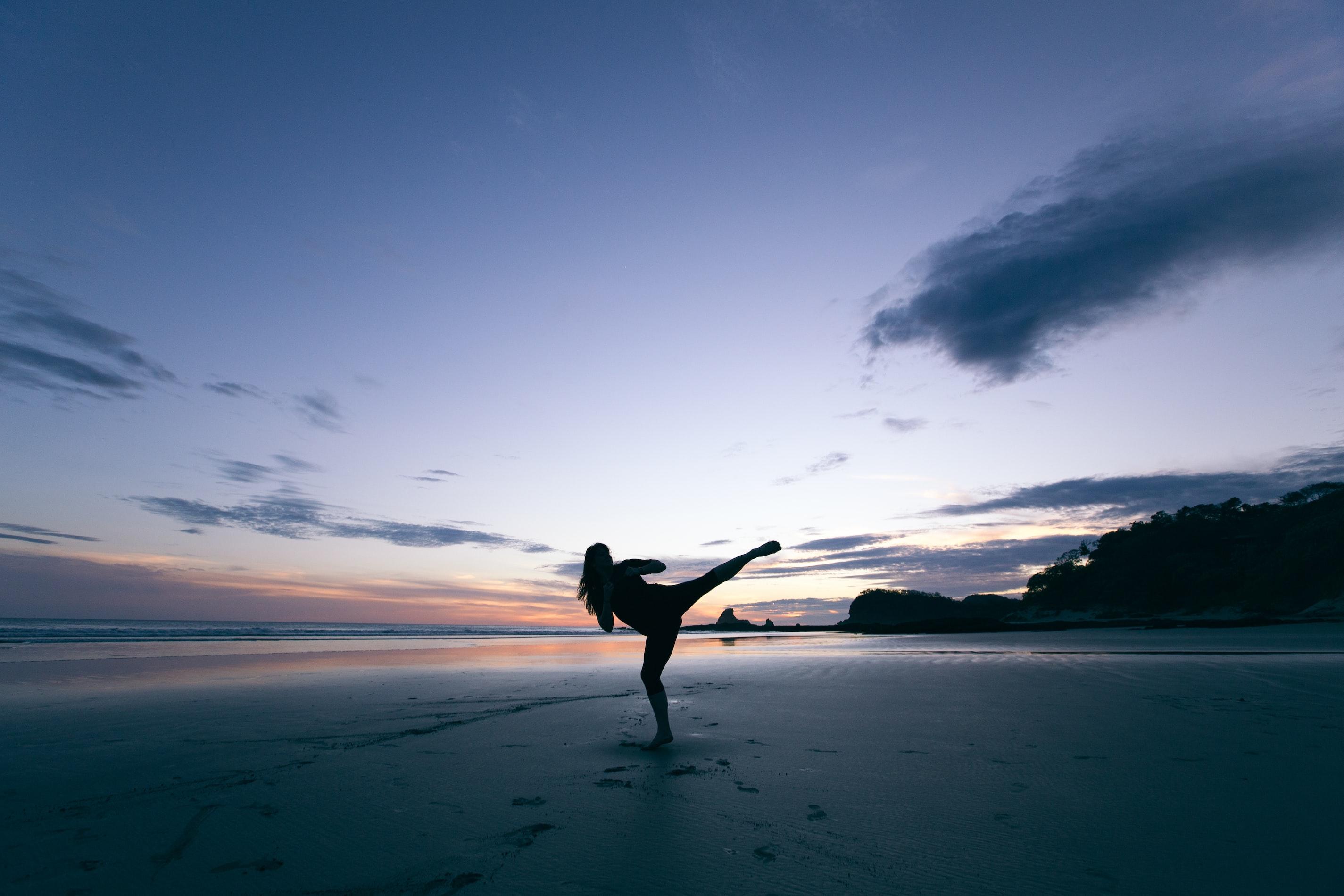 Person ist in Kampfpose bei Sonnenuntergang an einem Strand