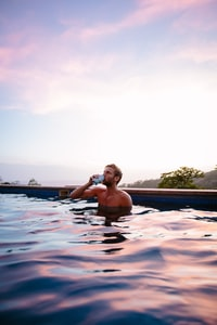 topless man drinking beverage while on swimming pool