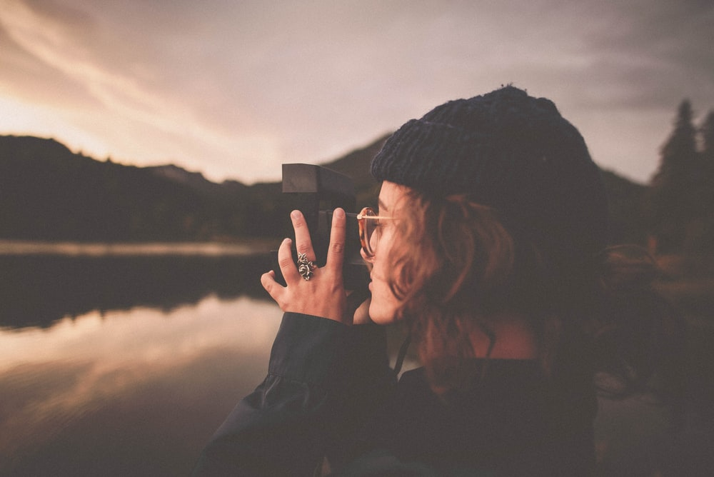 photograph of woman taking a picture of body of water