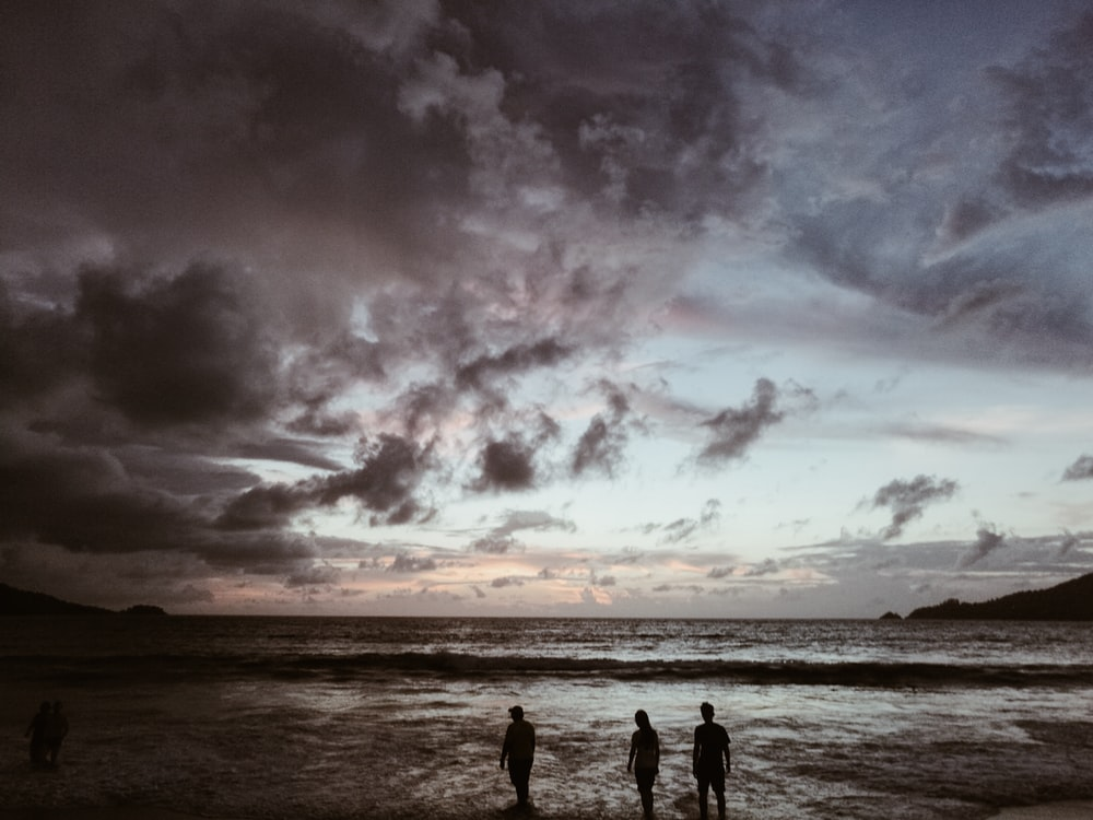 silhouette of three people on seashore under gray cloudy skies