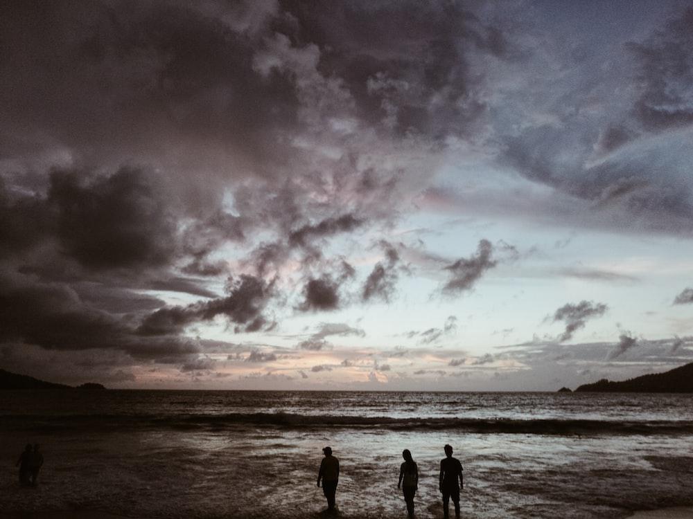 silhouette of three people on seashore under gray cloudy skies