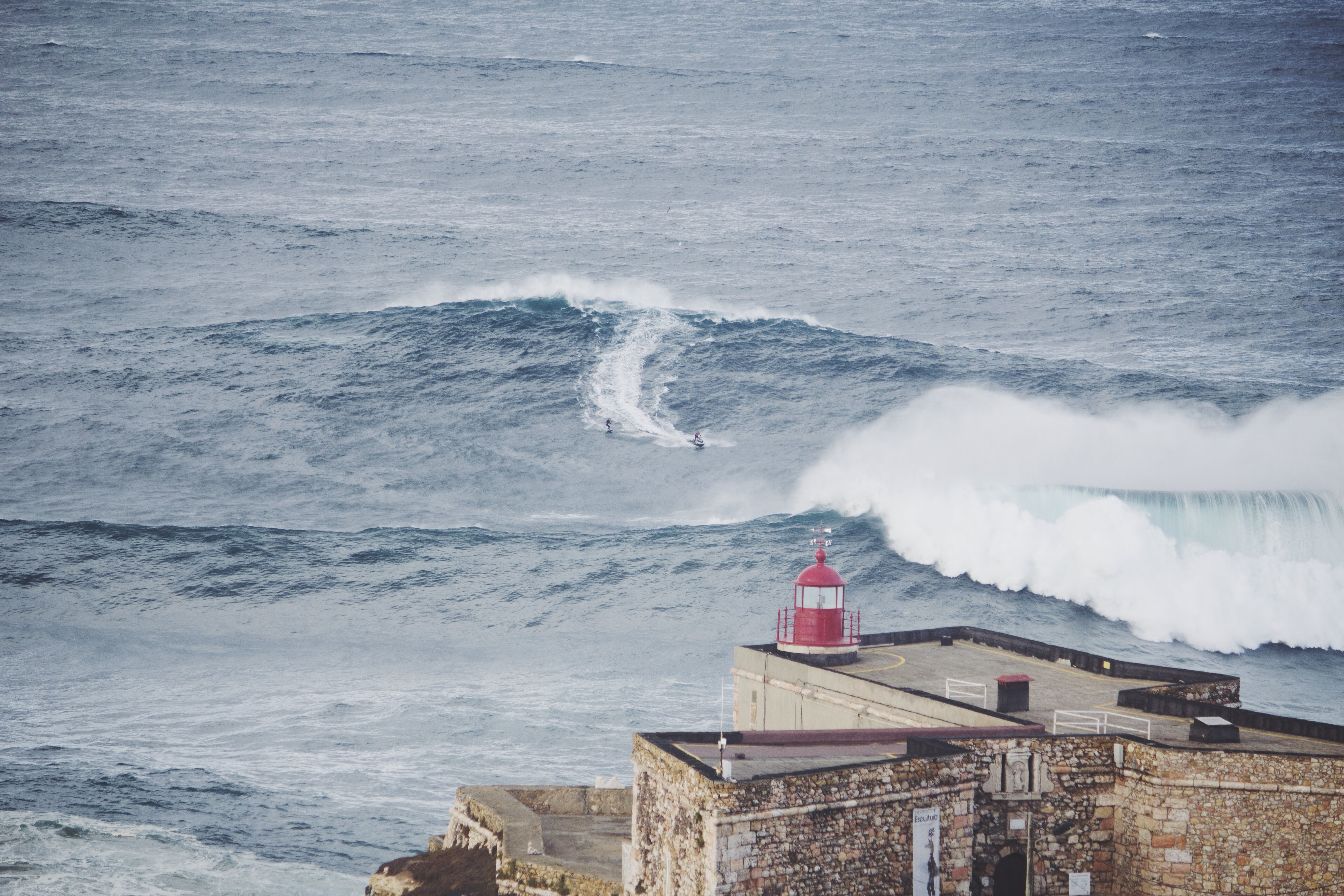 An ocean wave curling in the distance, in front of a coastal lighthouse at Nazaré