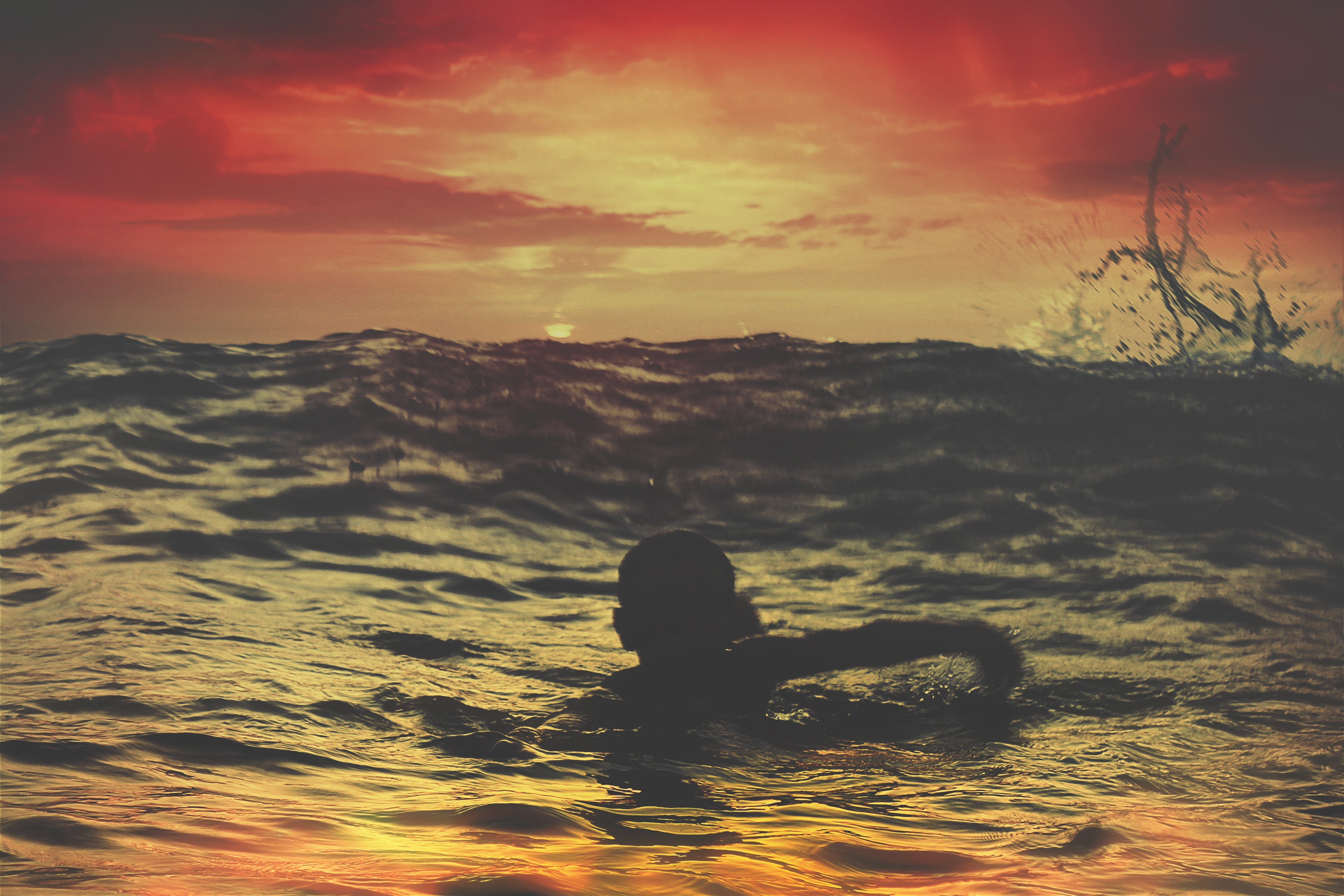 person swimming on body of water under red and orange sky