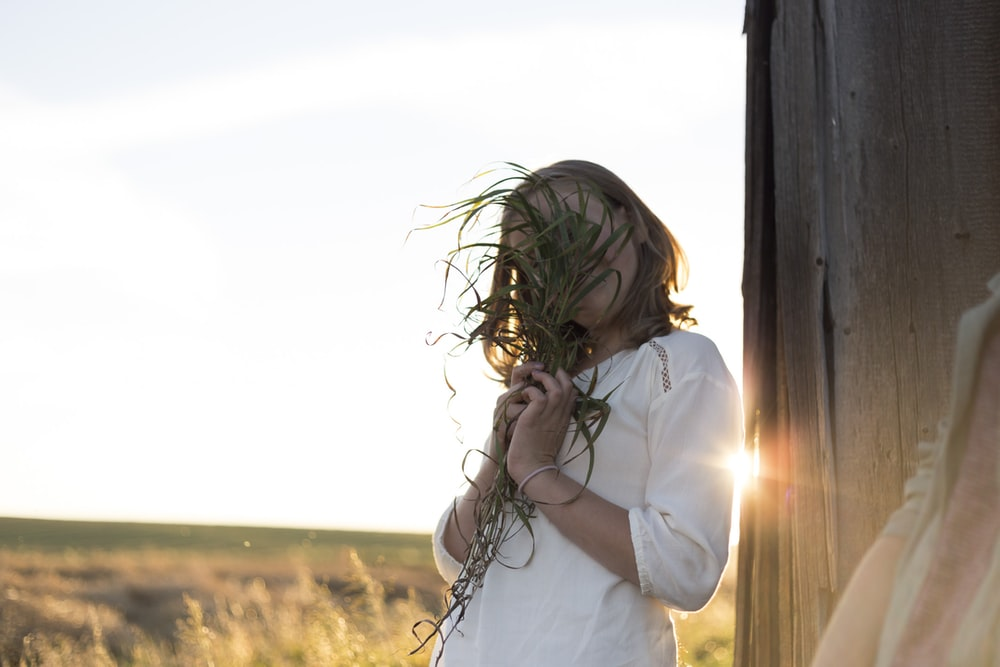 woman holding green plants