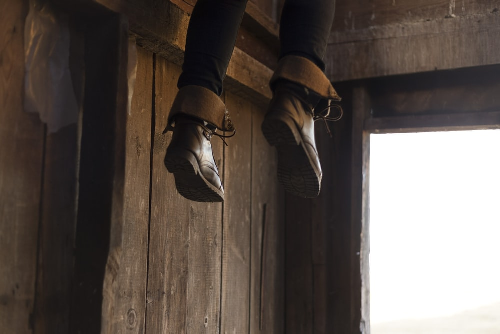 person feet with brown leather boots dangling by the entrance