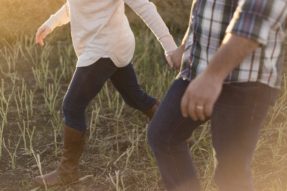 two person wearing denim pants on grass field