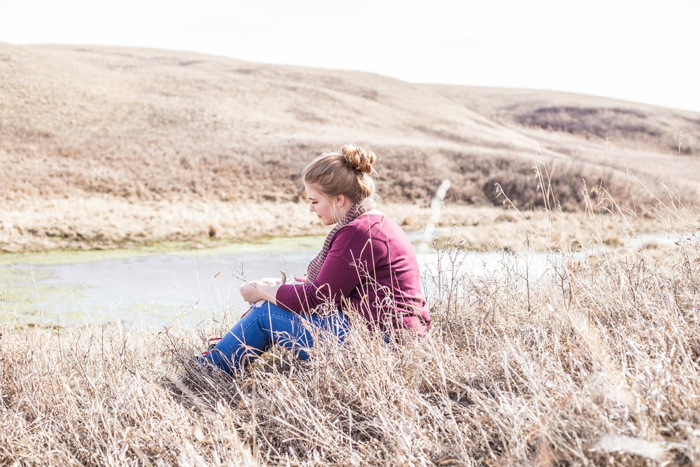 woman sitting on grass beside concrete road at daytime