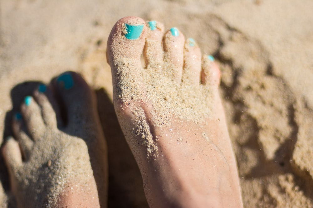 person sky-blue nail polish feet on brown sand