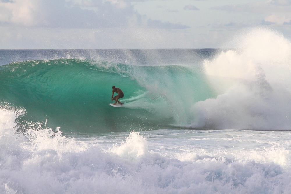 man riding surfboard under sea wave during daytime
