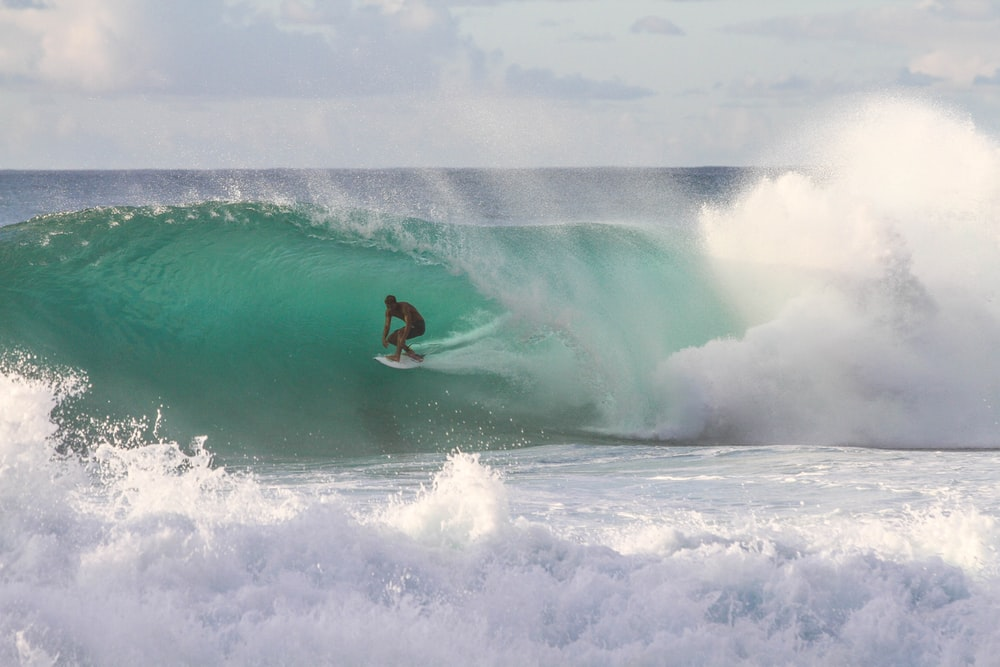 man riding surfboard under sea wave during daytime