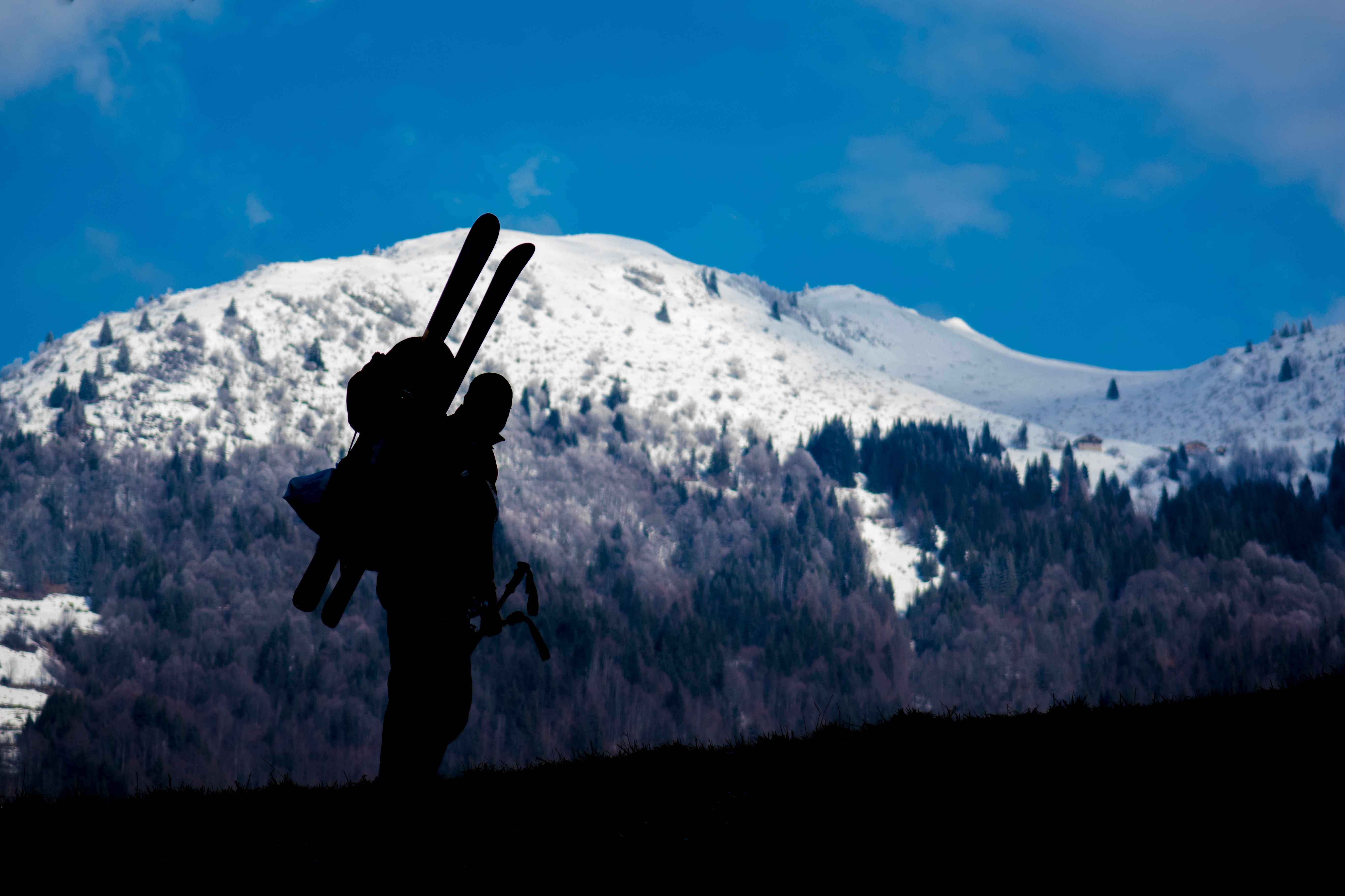 Silhouette of a skier ascending a snowy blue mountain landscape