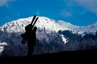 silhouette of person climbing mountain during daytime