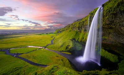 A beautiful landscape with green plains and a tall waterfall pouring from a moss-covered rock face