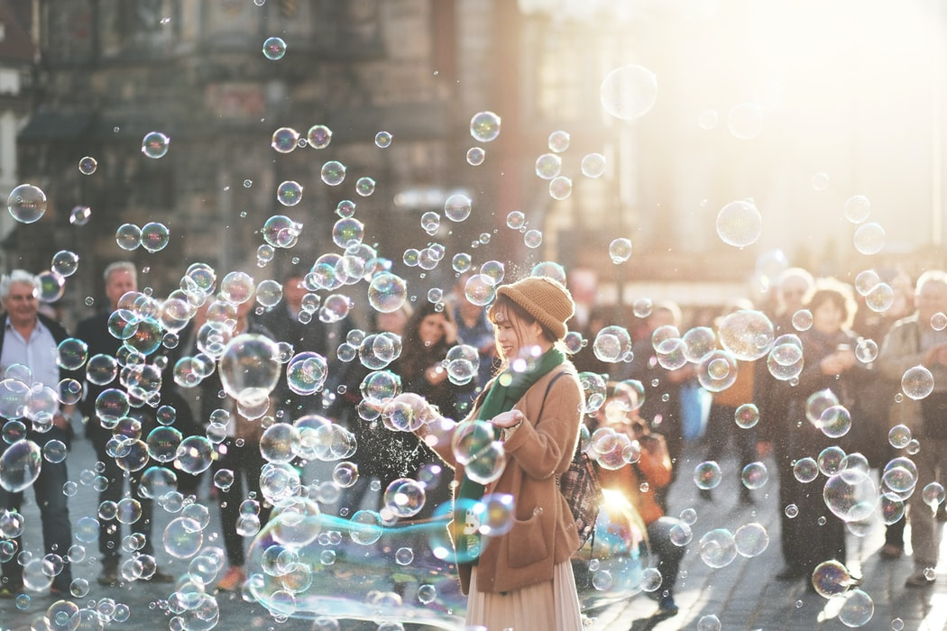A photo of a young woman standing on a street in a cloud of bubbles, smiling. The sun is shining on her and caught in the bubbles, so it looks kind of magical.