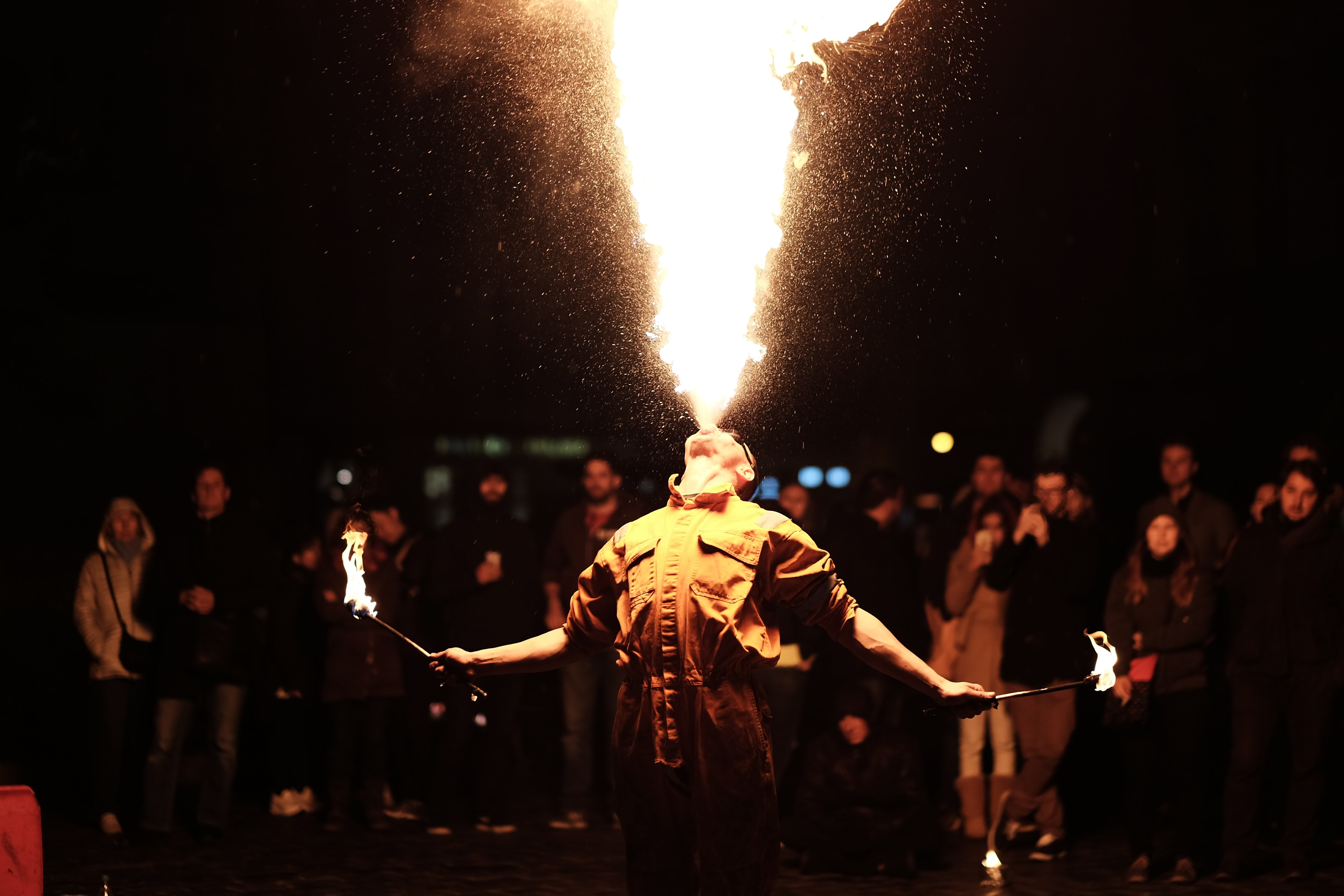 Man holding torch and blowing fire out of mouth with people standing behind him