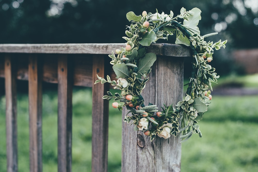 photo of green flower wreath hang on gray wooden baluster outdoors during daytime