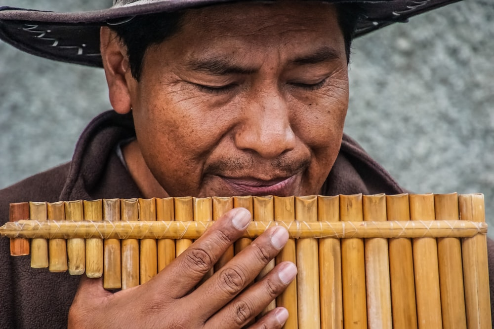 man playing wooden wind instrument