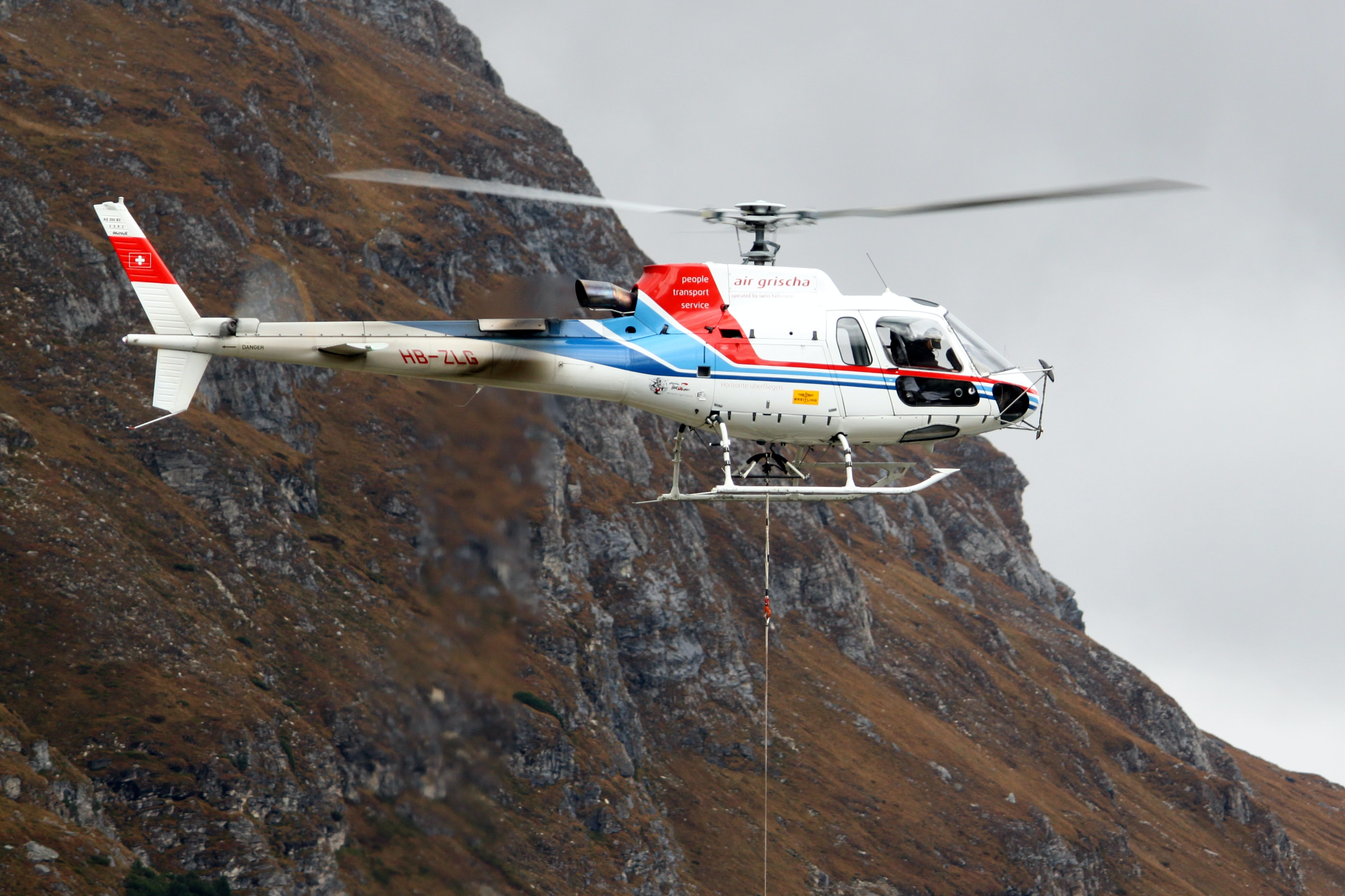 White, blue, and red helicopter rescue in Lago di Lei