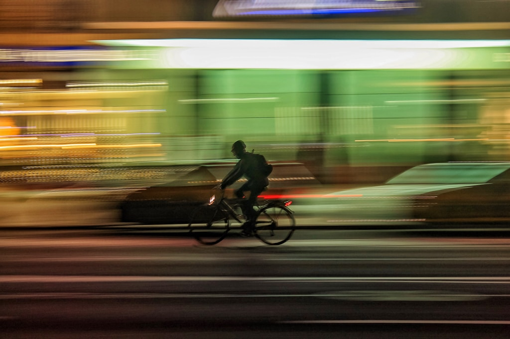 time lapse photo of person riding bicycle on road
