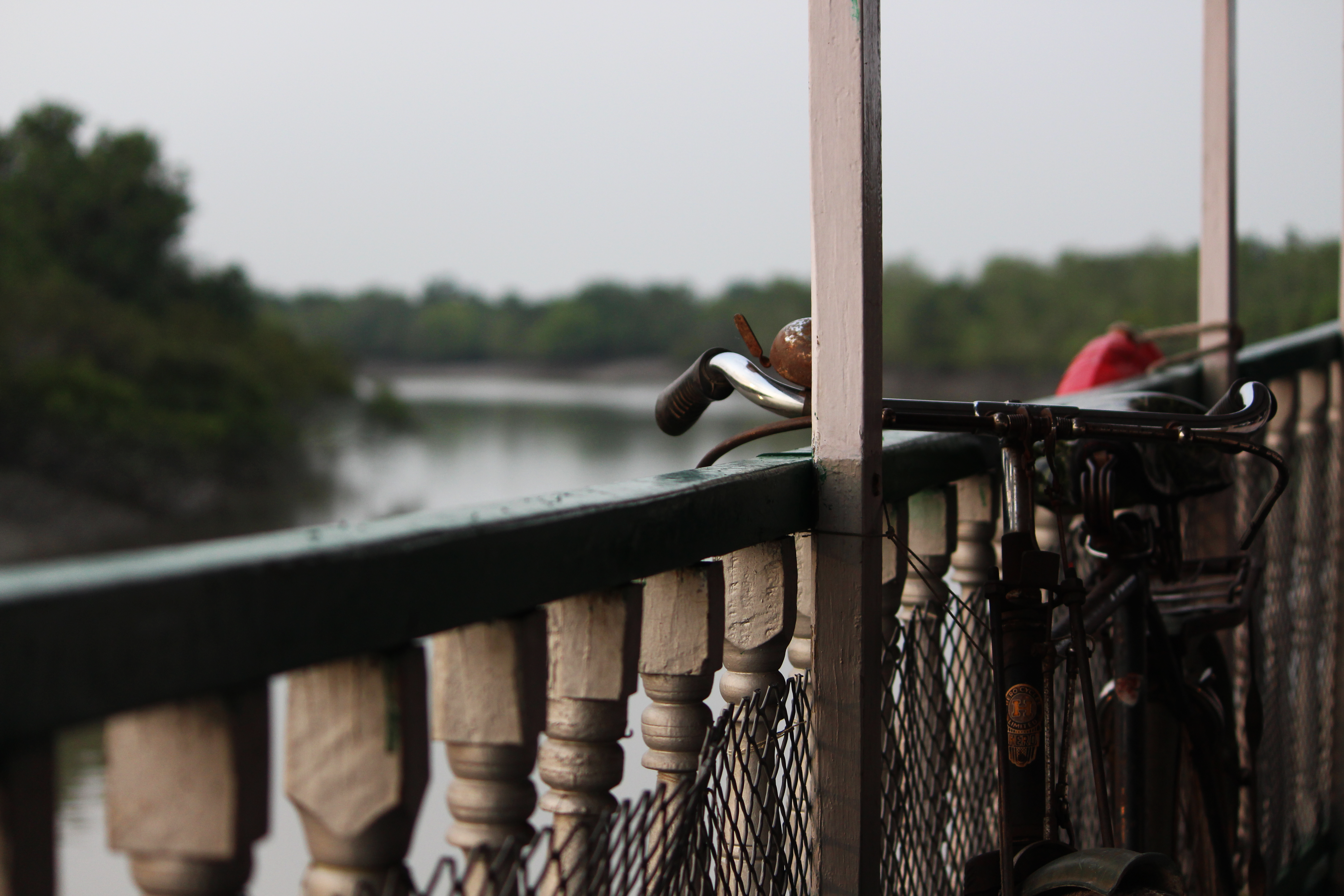 A bicycle leaning against a balustrade over a lake
