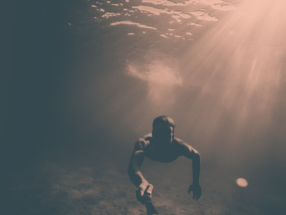 man holding black monopod while under the sea